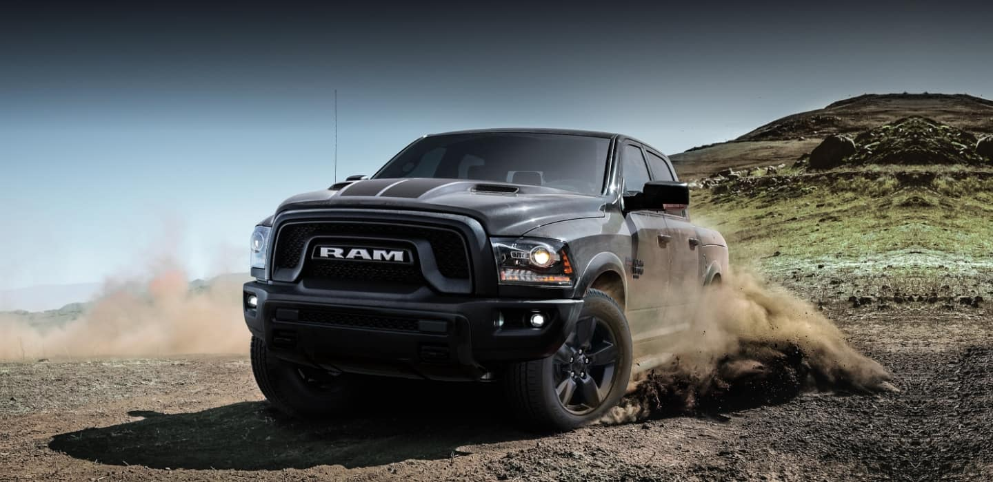 The 2019 Ram 1500 Classic kicking up dust from its wheels as it's driven down a hill.