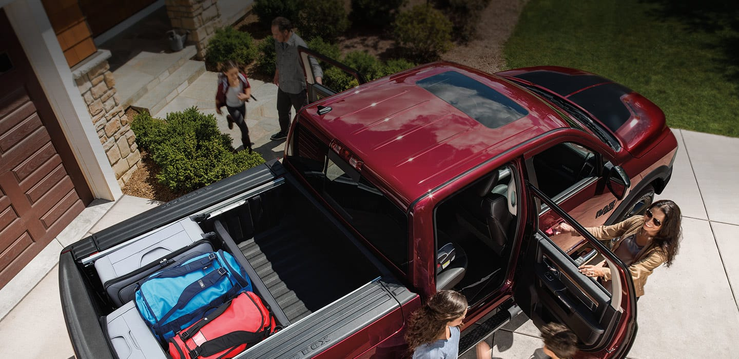 An overhead view of a 2019 Ram 1500 Classic Warlock with the second row doors open. Several bags are stored in the truck bed and a family is getting into the vehicle.