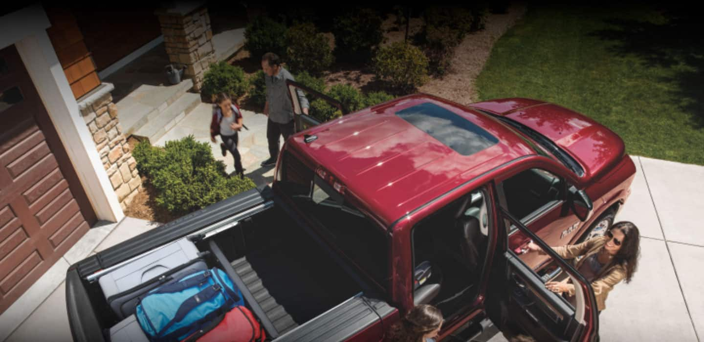 An overhead view of a family getting into their Ram 1500 Classic Laramie. Parents have rear doors opened for the two children to get in. Luggage is sectioned off in the bed.