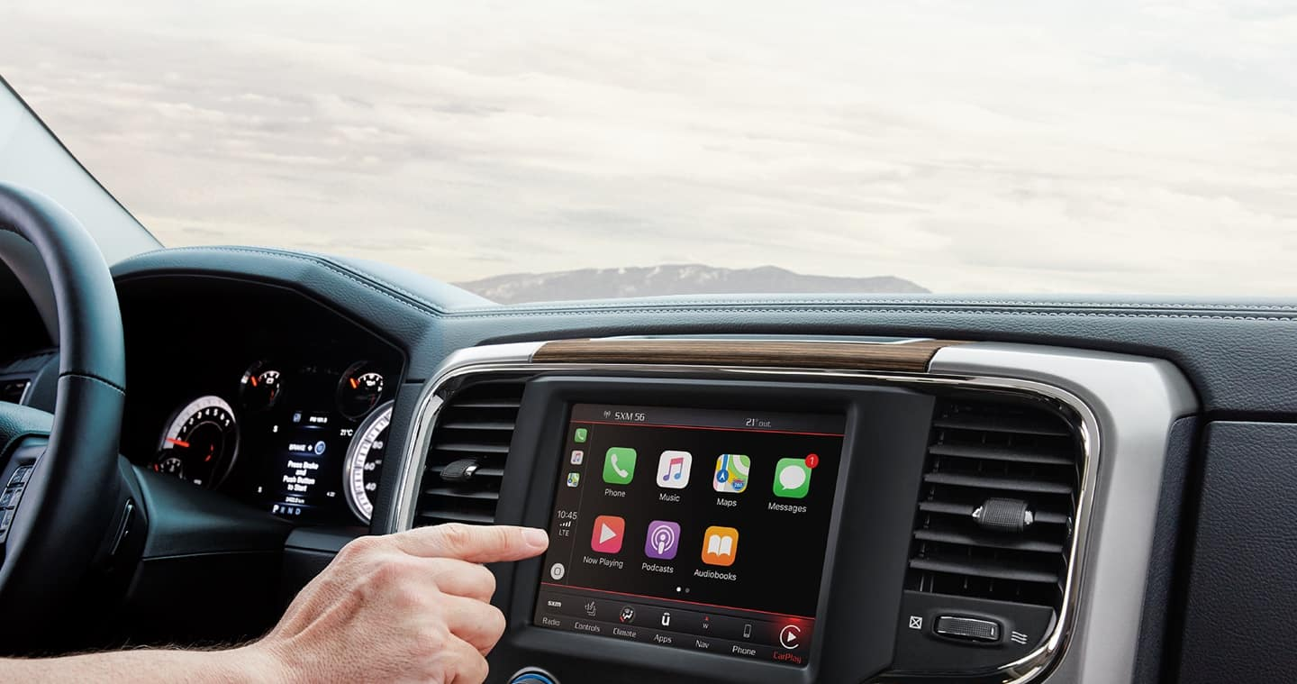Uconnect touchscreen with hand reaching for Apple CarPlay selections on-screen.