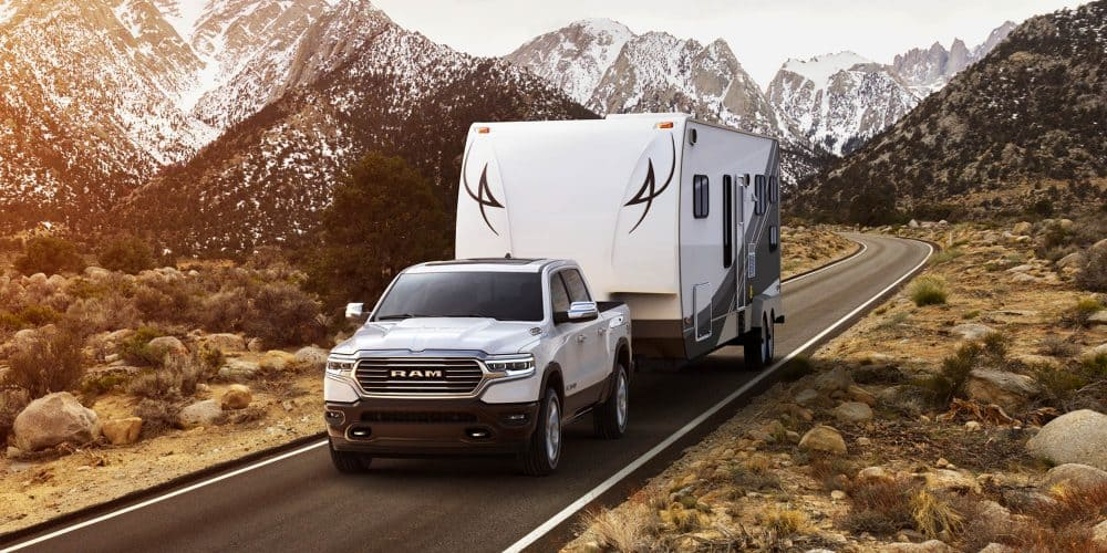 White 2019 Ram 1500 towing trailer with snowy mountains in background