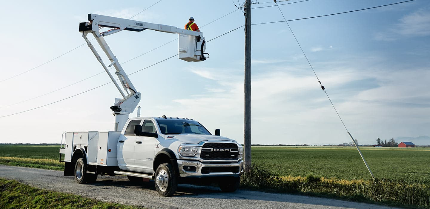 Display 2019 Ram Chassis Cab equipped with a boom lift. A worker is on the platform of the lift and working on a telephone wire.