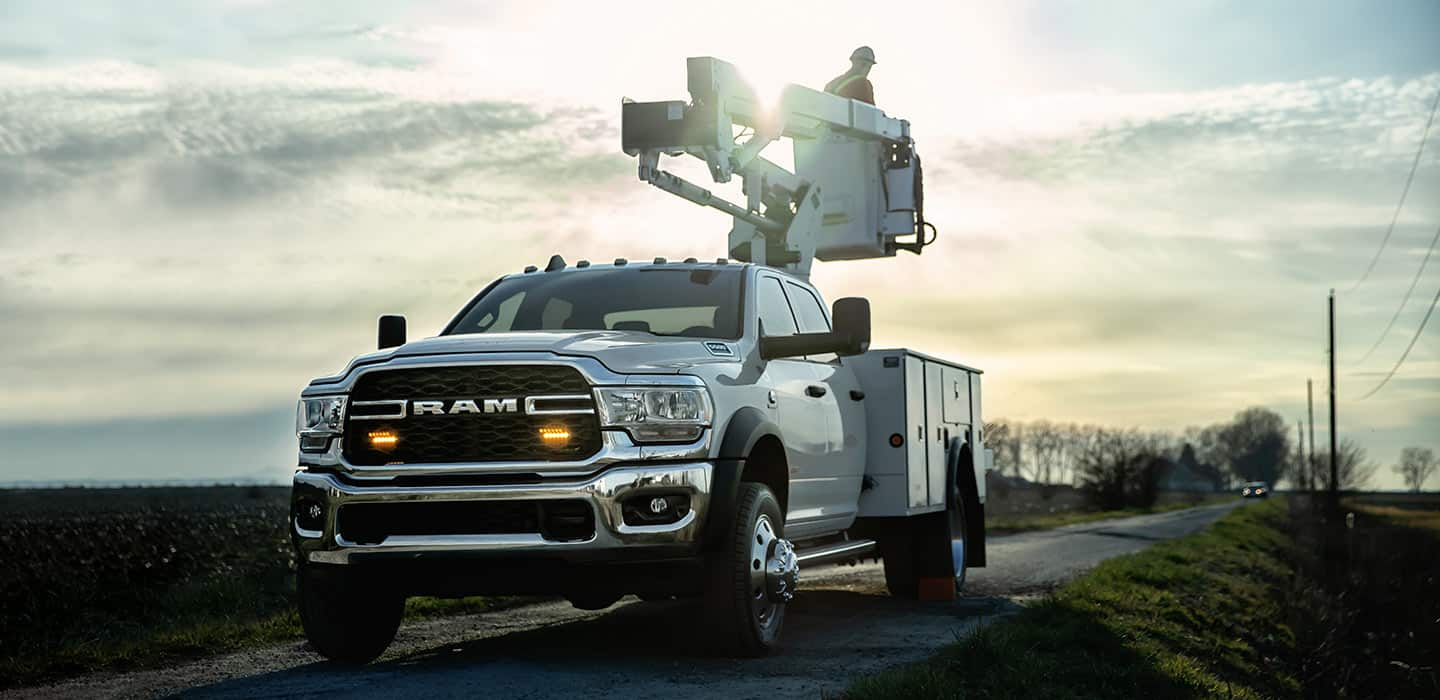 Display 2019 Ram Chassis Cab equipped with a boom lift. The lift is lowered and a worker is in its cockpit.