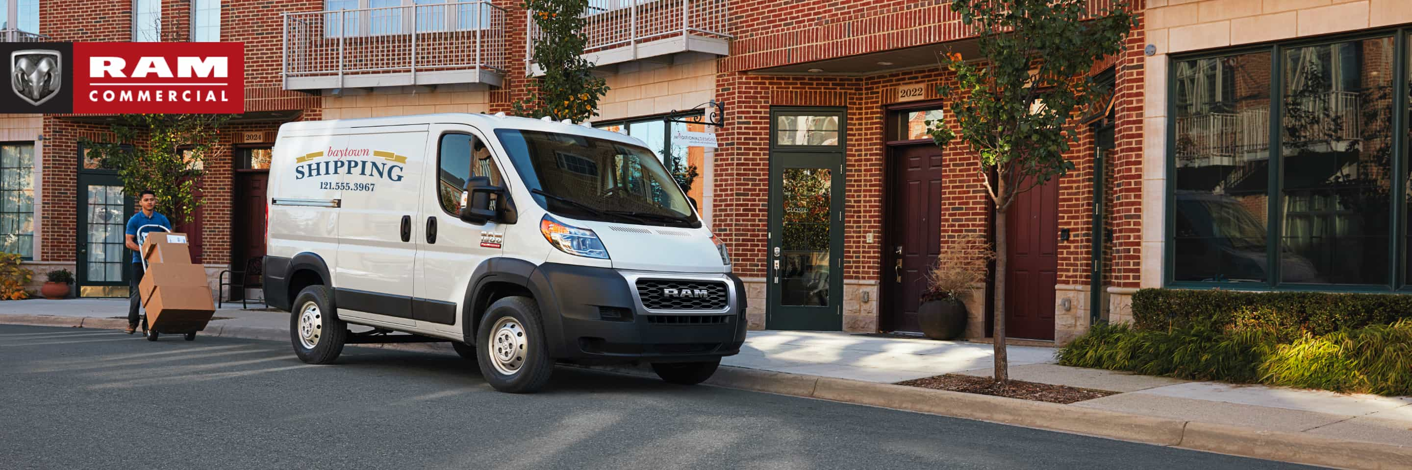 A 2019 Ram ProMaster with a shipping company logo parked outside a brick building. The Ram Commercial logo.