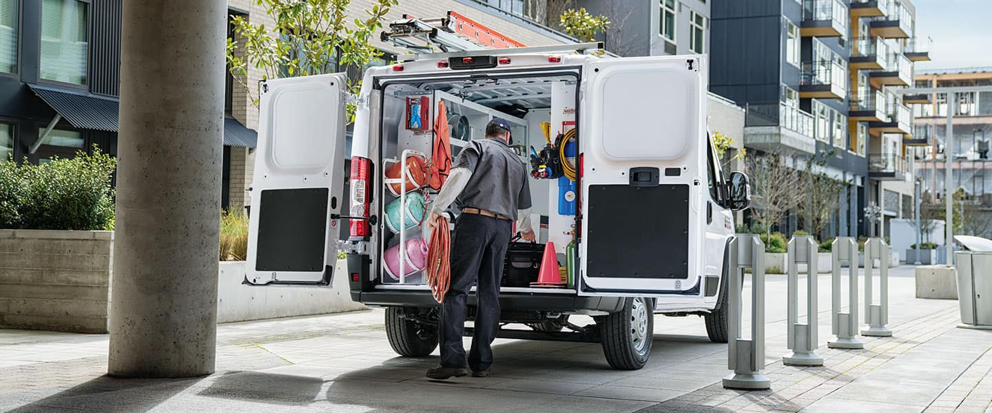 Ram ProMaster parked on a city street with rear doors open. A man is unloading equipment from the packed cargo area.