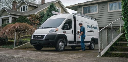 Ram ProMaster with custom graphics parked in a driveway.
