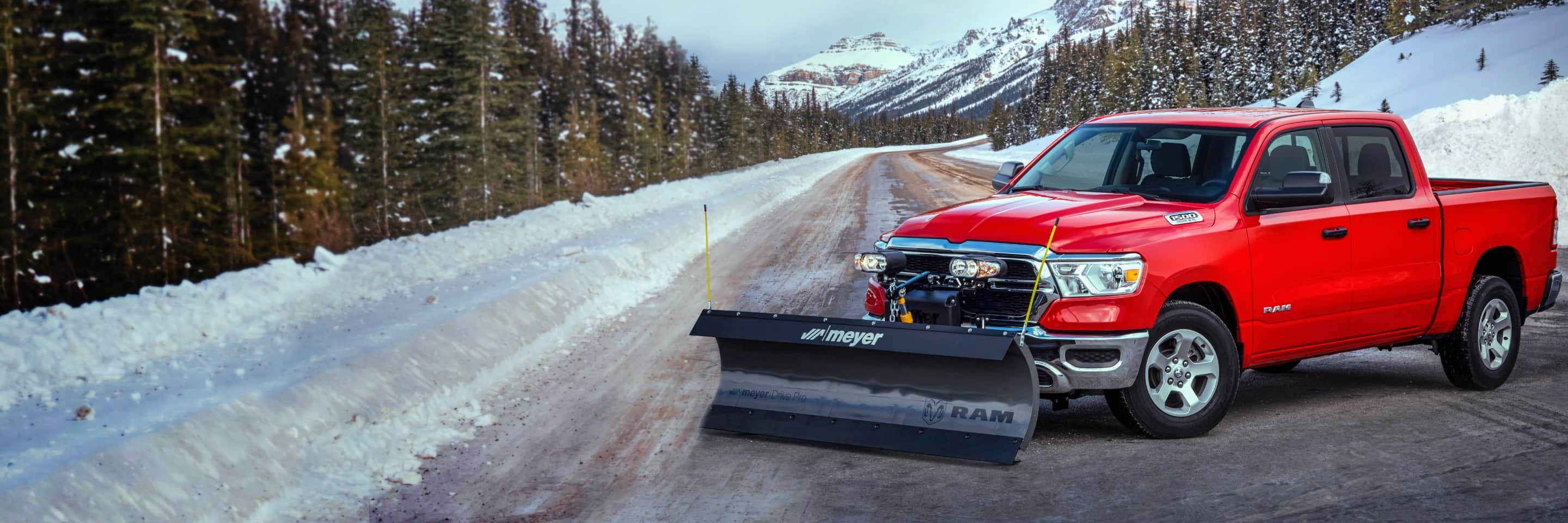 The 2020 Ram 1500 with a snowplow upfit parked across the width of a plowed mountain road.