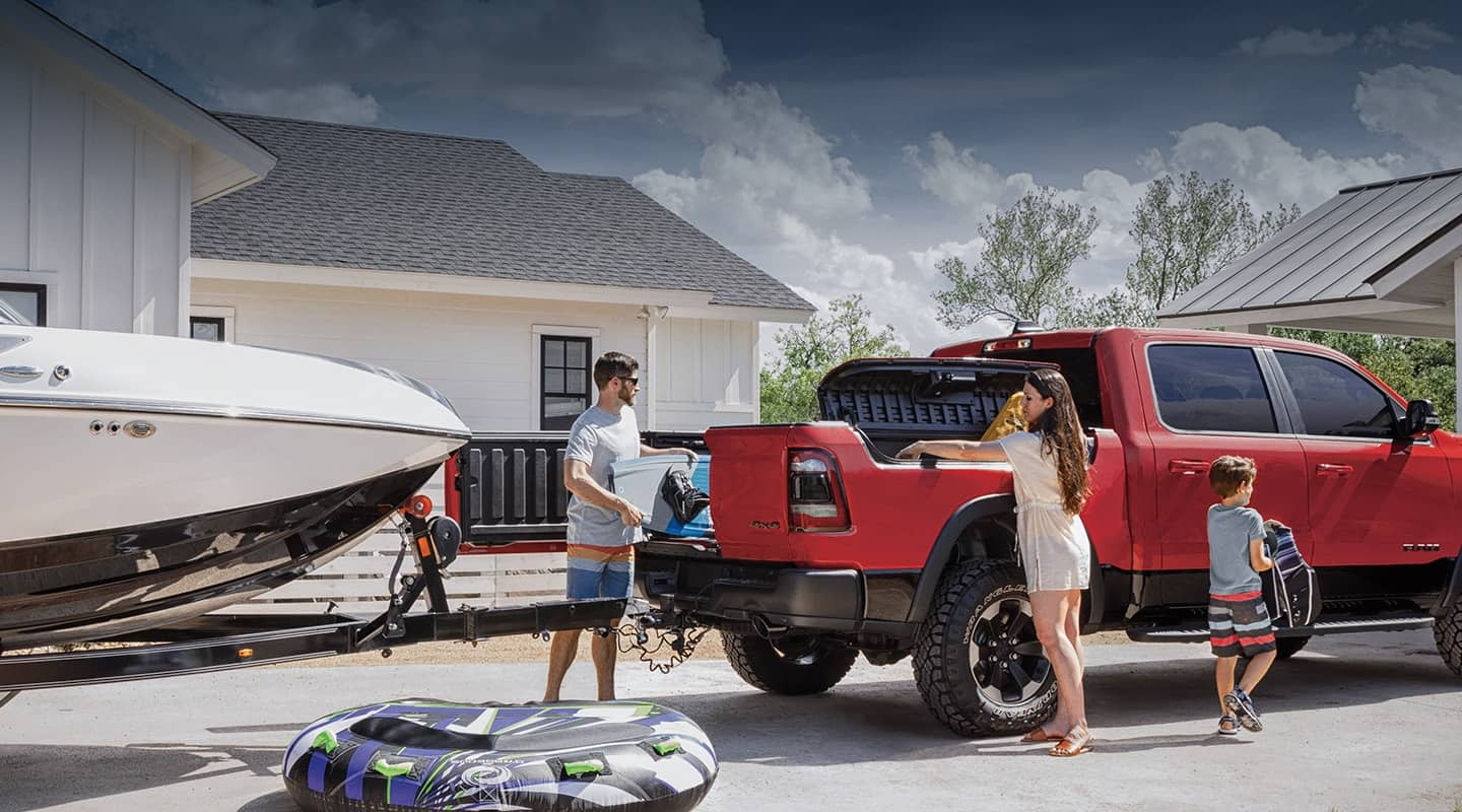 A 2020 Ram 1500 parked in a driveway, ready to tow a boat. A family is loading cargo into the pickup bed and the RamBox.