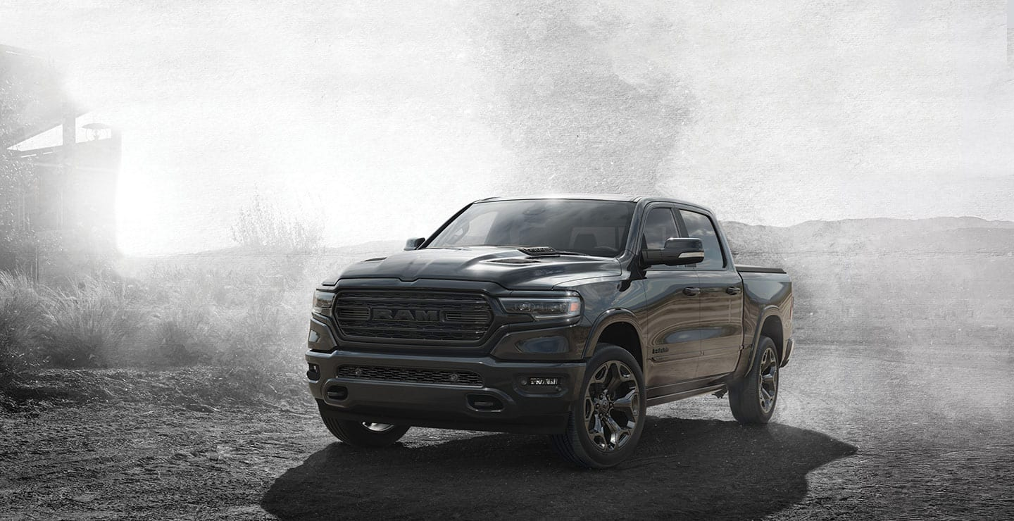 A three-quarter front view of a 2020 Ram 1500 parked on gravel in a dusty desert setting.