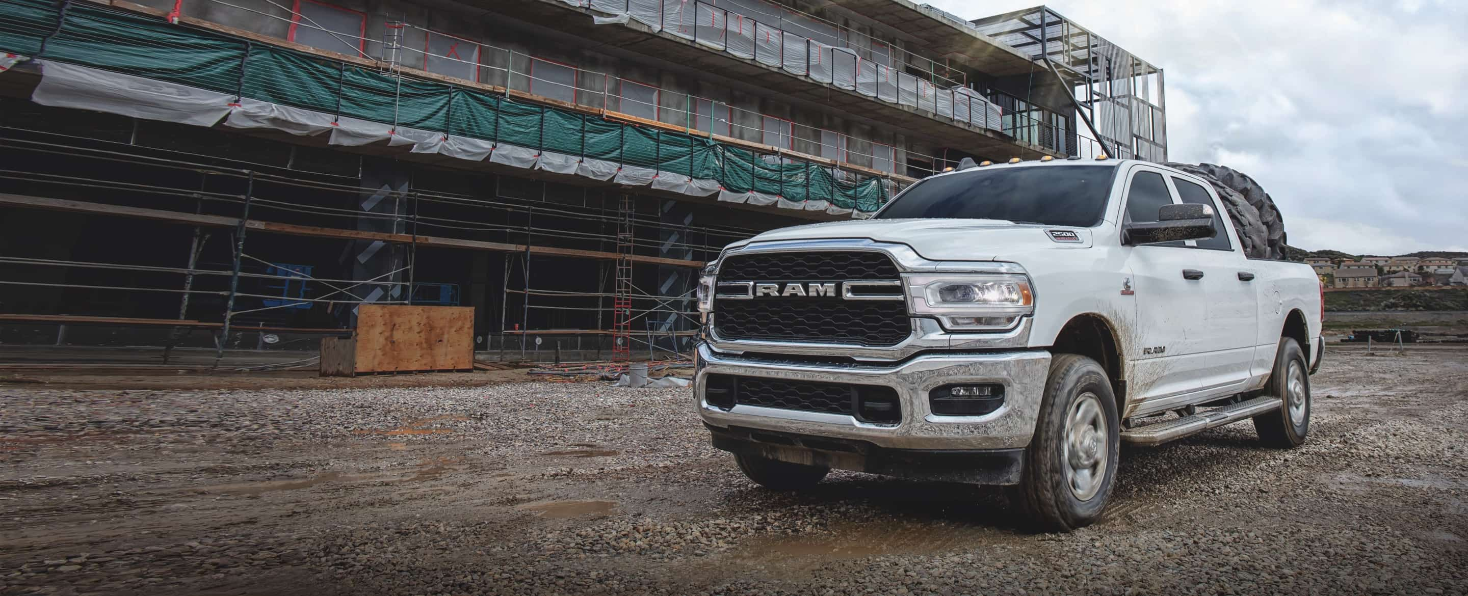 A 2020 Ram 2500 parked on a construction site with its pickup bed loaded with tires.