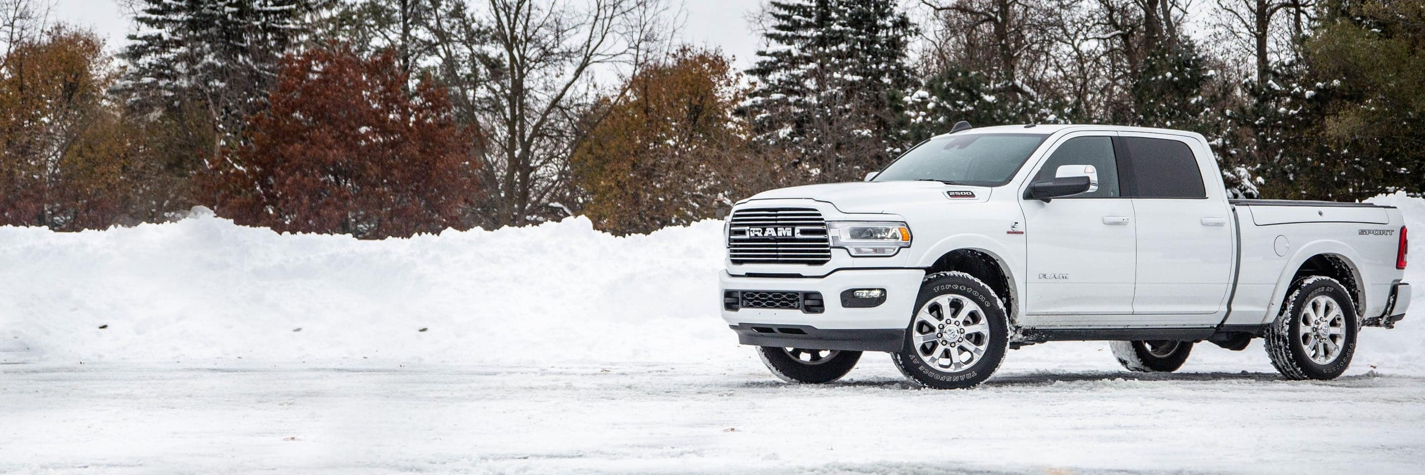 The 2020 Ram 2500 Laramie parked on a snow-covered road against a backdrop of snow-dusted trees.