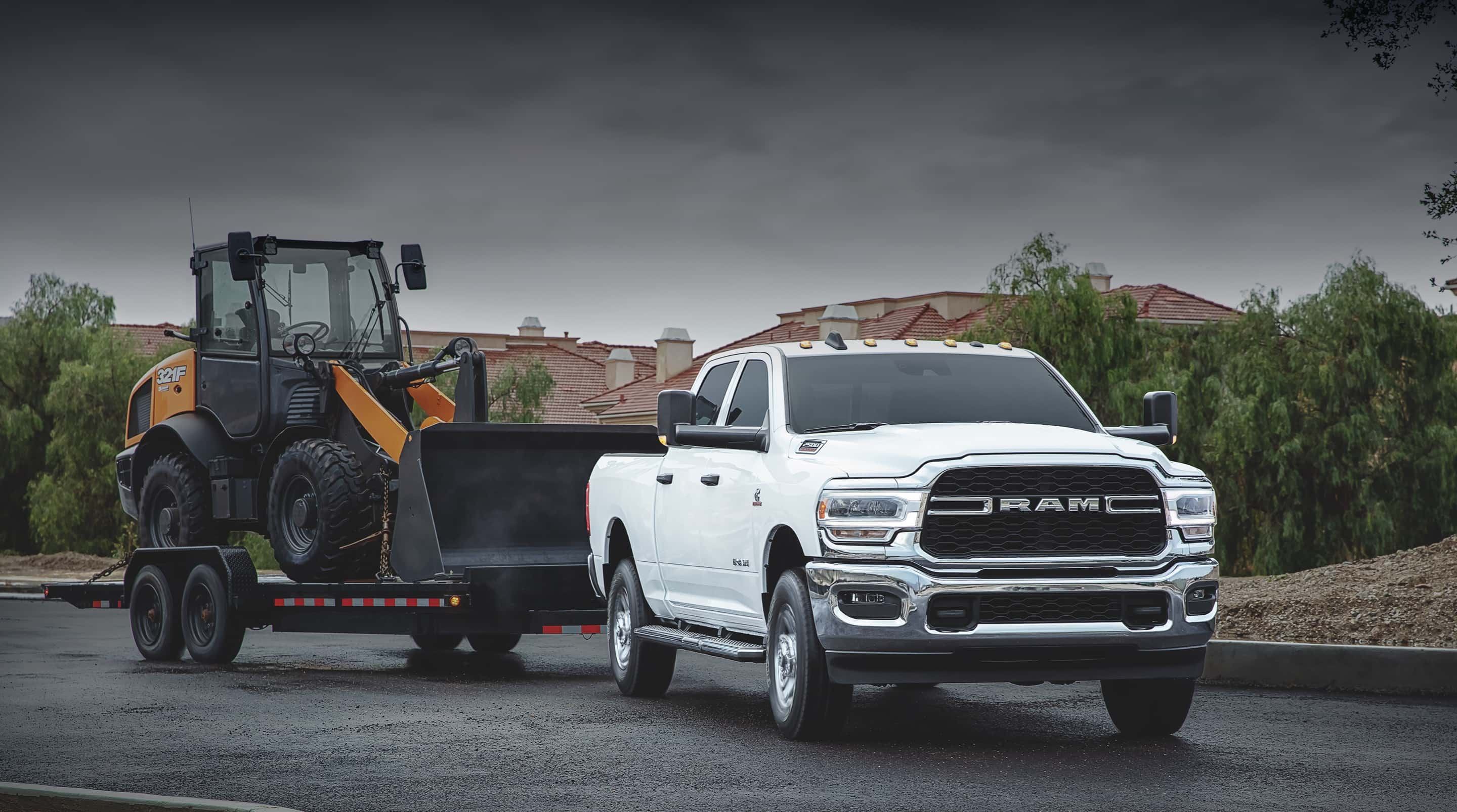 The 2020 Ram 2500 towing a flatbed trailer with a front loader on it.