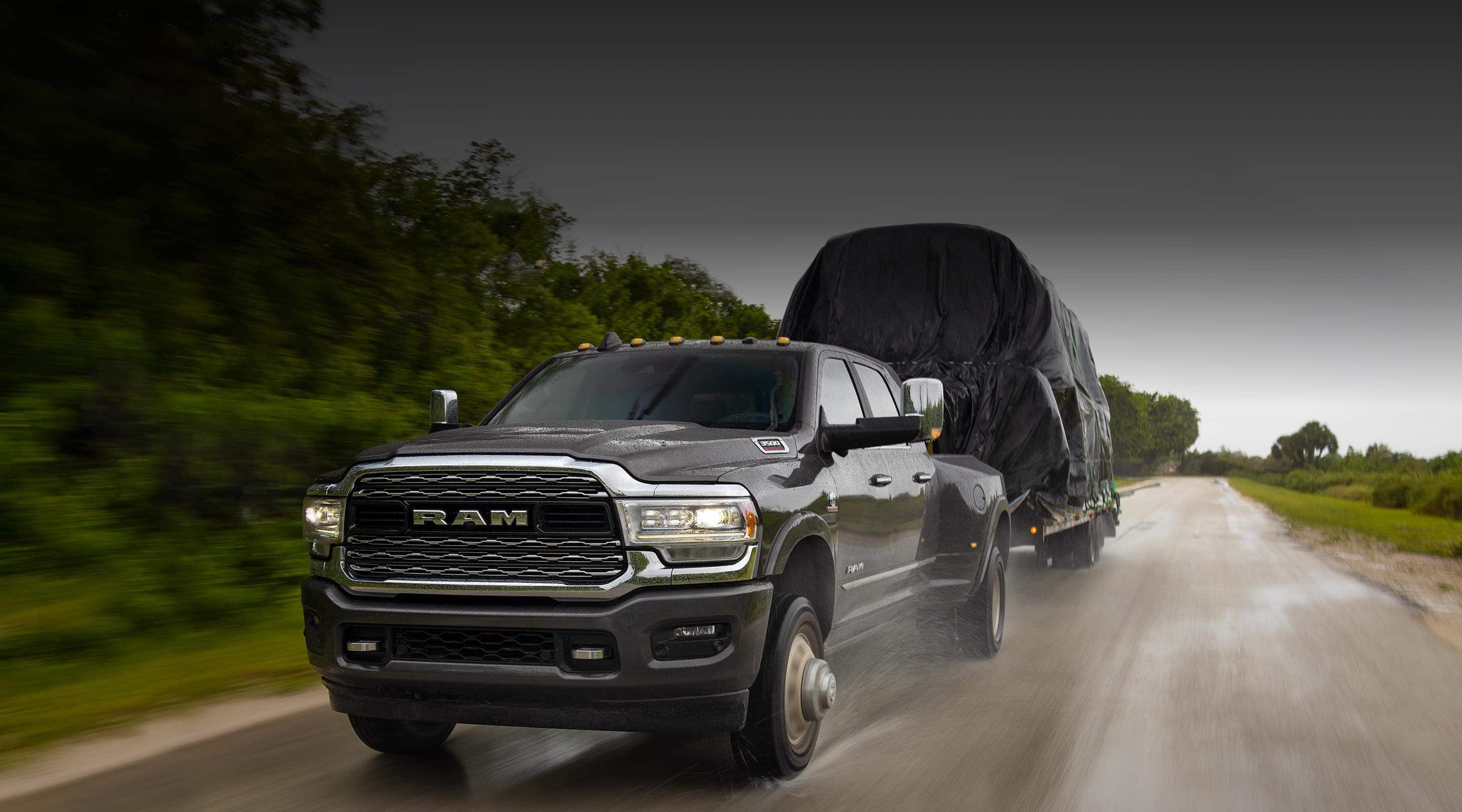 The 2020 Ram 3500 towing a trailer in the pouring rain.