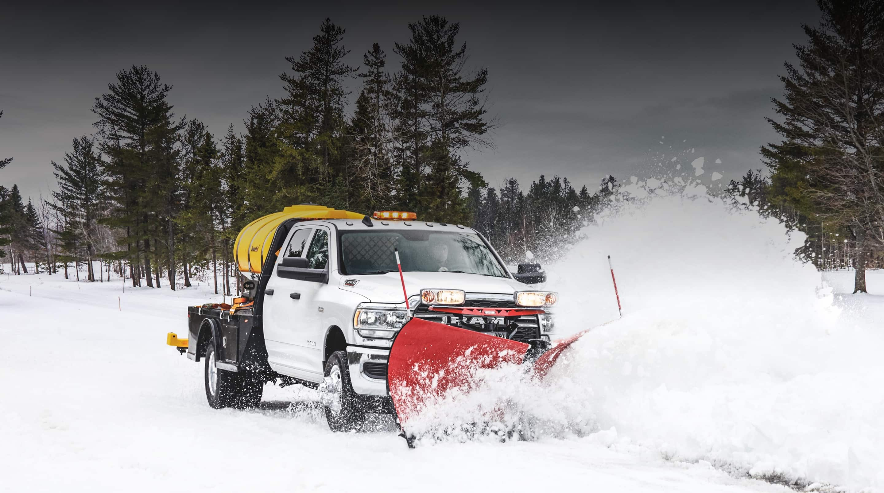 A 2020 Ram Chassis Cab with a snow plow upfit clearing a path through the snow.