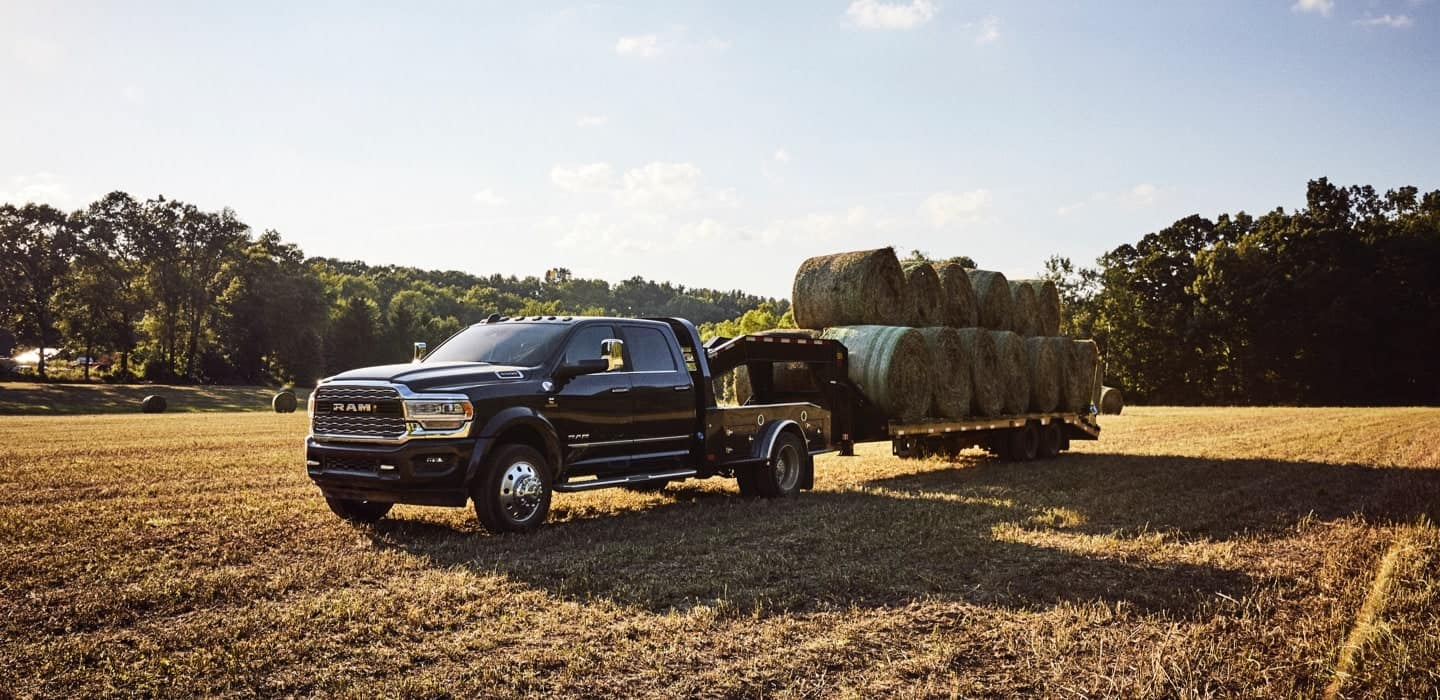 Display The 2020 Ram Chassis Cab parked in a field, towing a trailer loaded with bales of hay.
