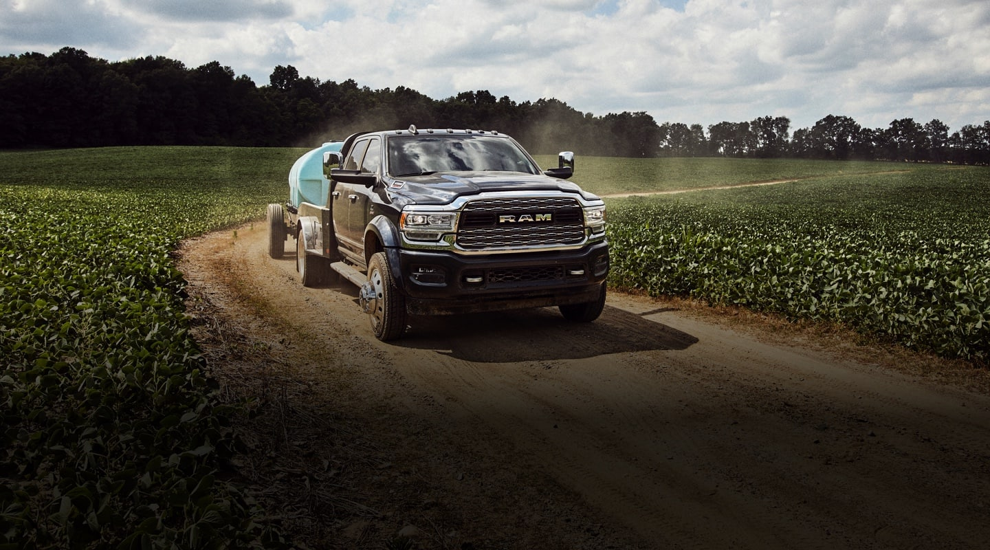 The 2020 Ram Chassis Cab being driven on a dirt road through farmland.