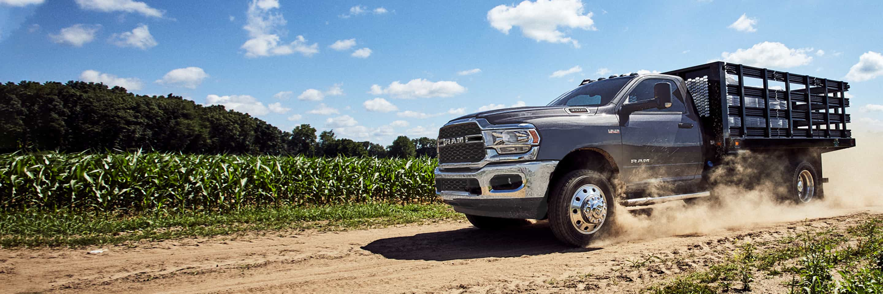 The 2020 Ram Chassis Cab kicking up dust as it is driven through a cornfield.