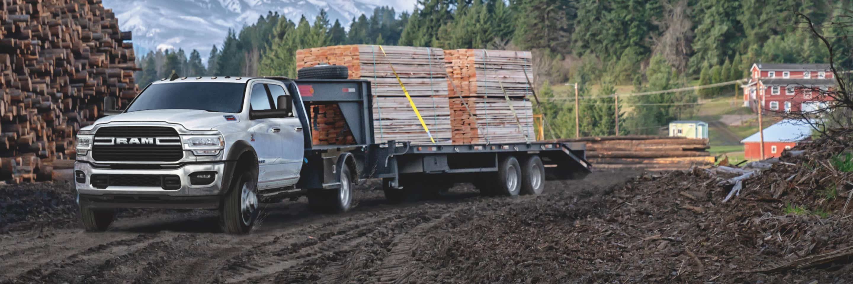 A 2020 Ram 5500 Chassis Cab SLT at a logging camp, towing a trailer filled with lumber.