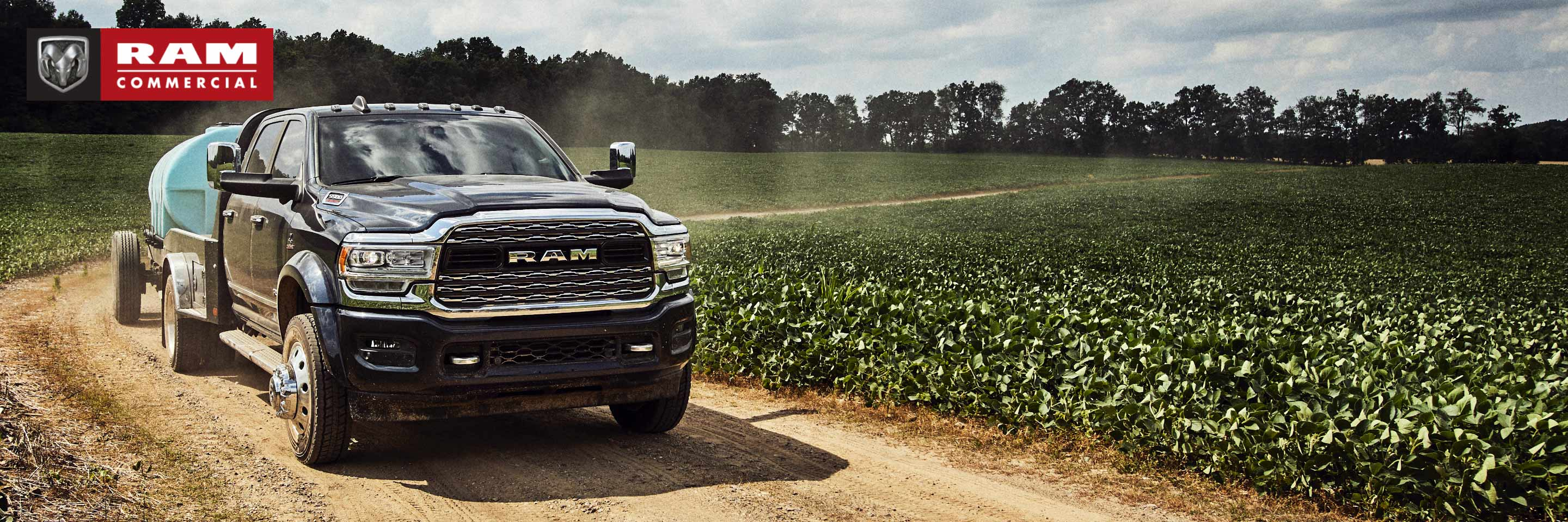 The 2020 Ram Chassis Cab being driven on a dirt road through a field with a water tank in tow. Ram Commercial logo.