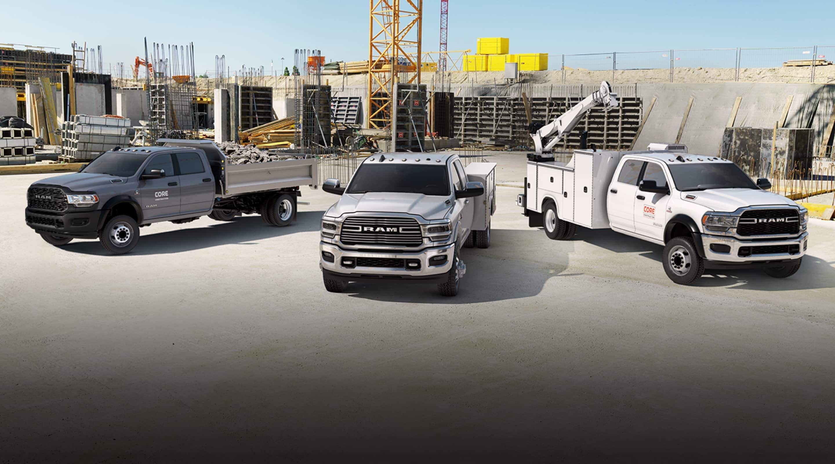 Three 2020 Ram Chassis Cab vehicles parked in a large construction site.