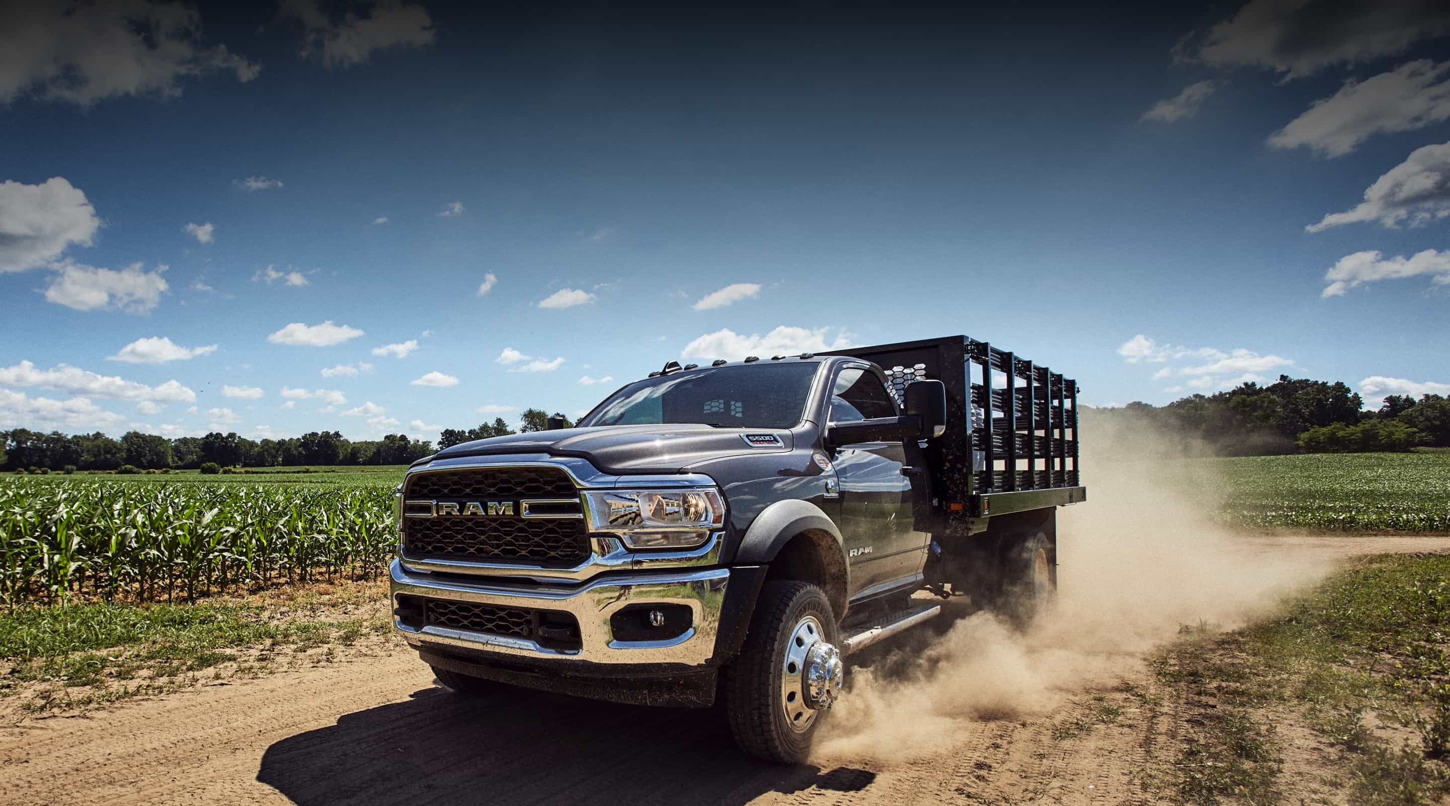 A grey Ram 4500 Chassis Cab with rancher upfit drives briskly down a rural dirt road.