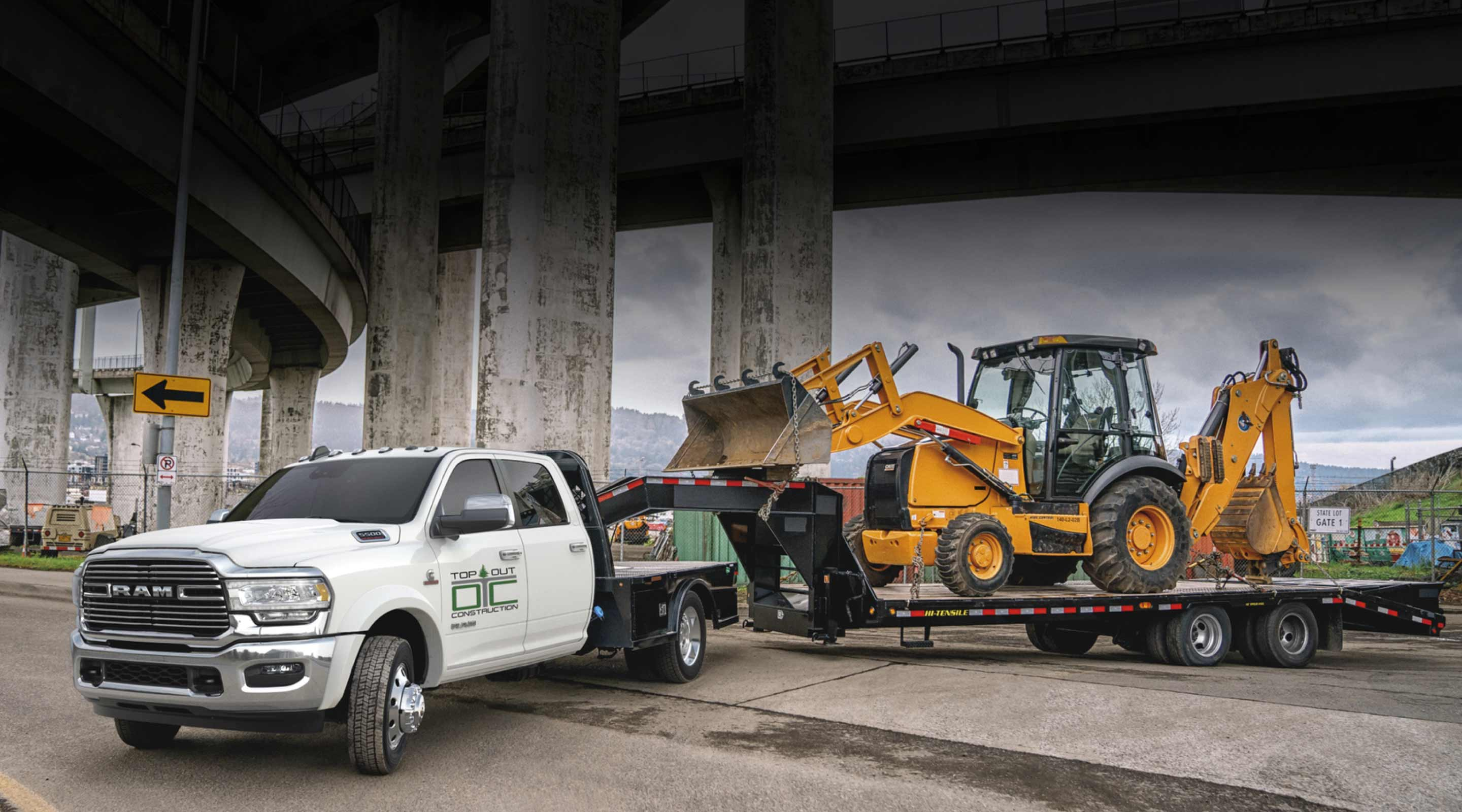 A 2020 Ram Chassis Cab towing a backhoe on a flatbed trailer.