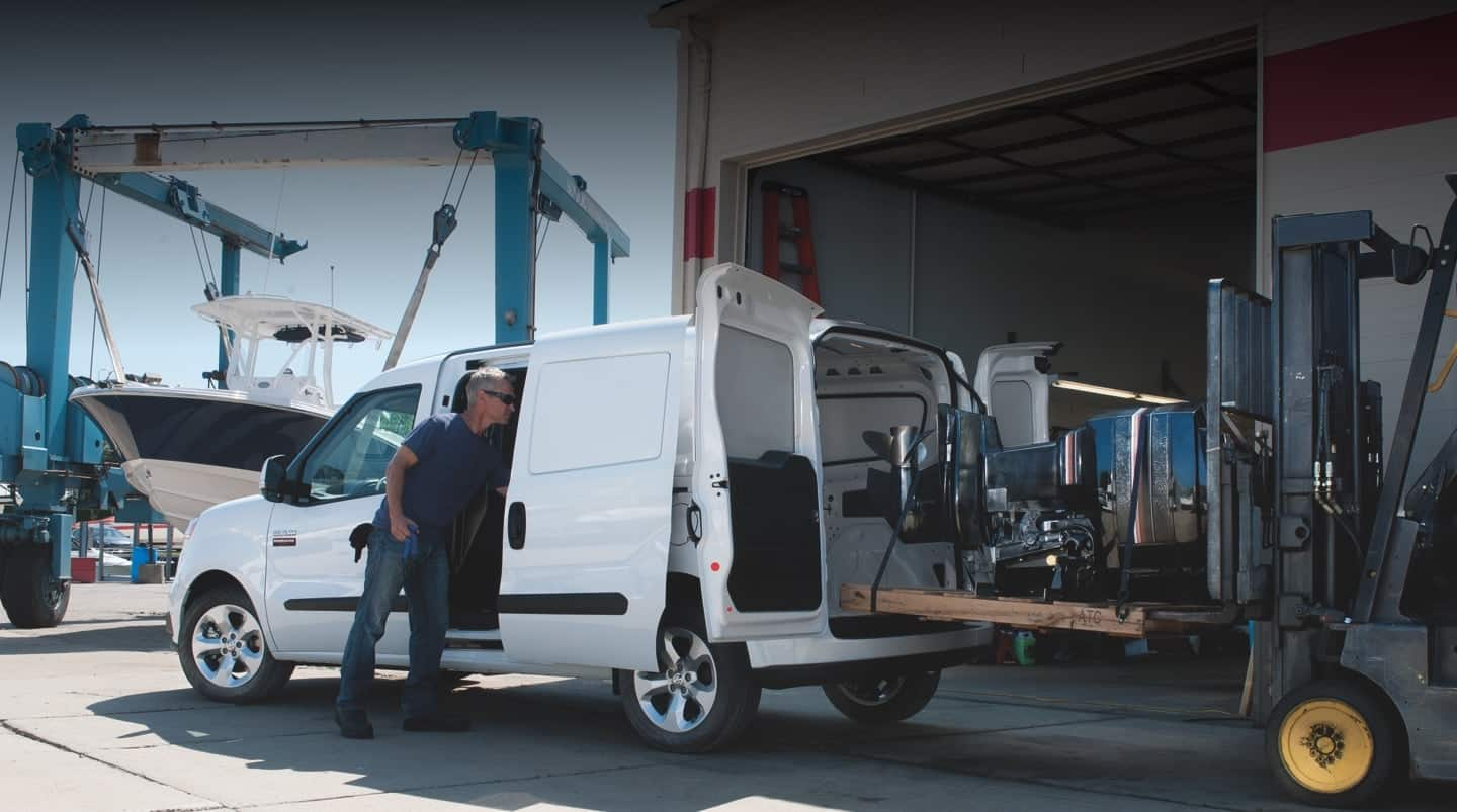 A 2020 Ram ProMaster City with the side and rear doors open and heavy equipment being loaded in the van.
