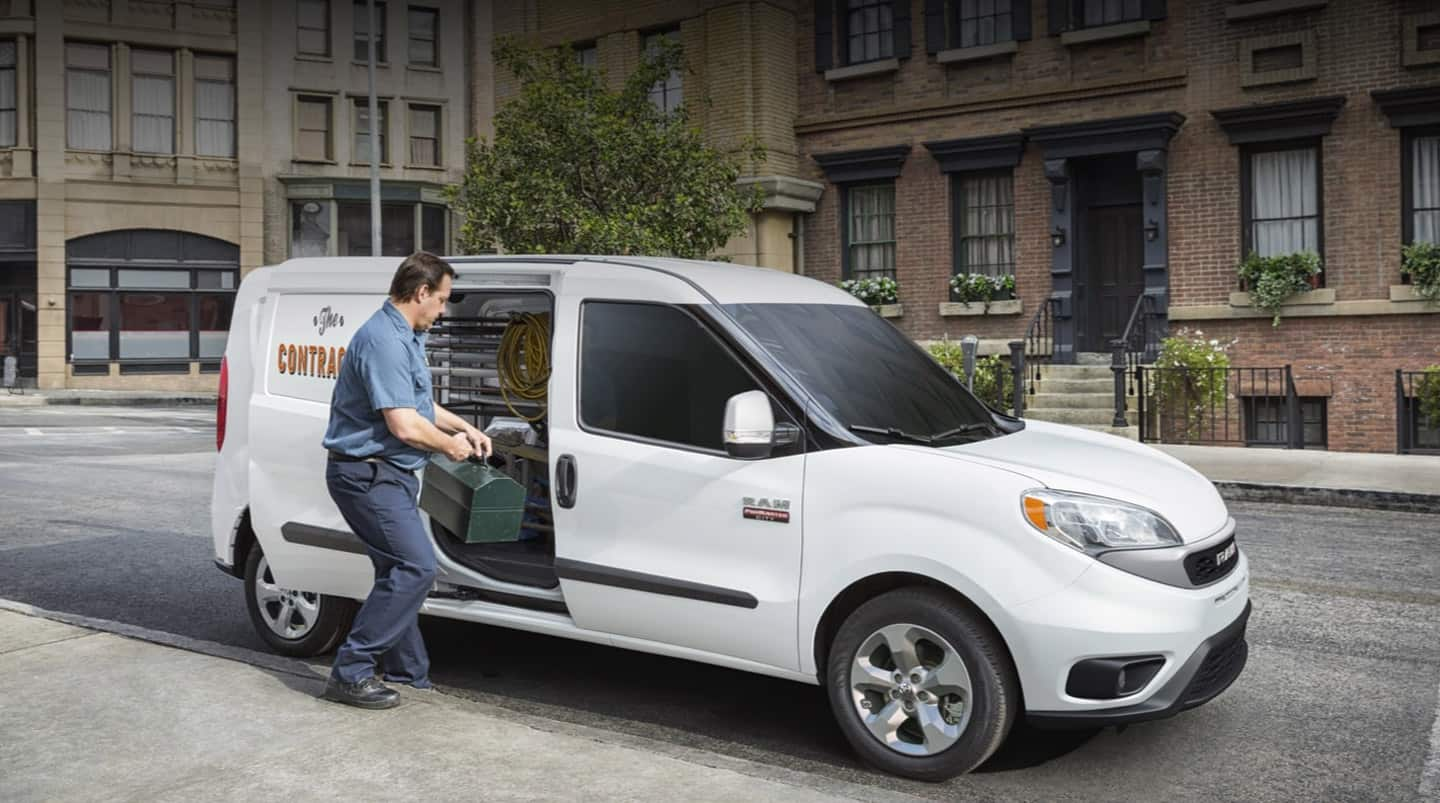 A man loading a toolbox through the side door of the 2020 Ram ProMaster City.