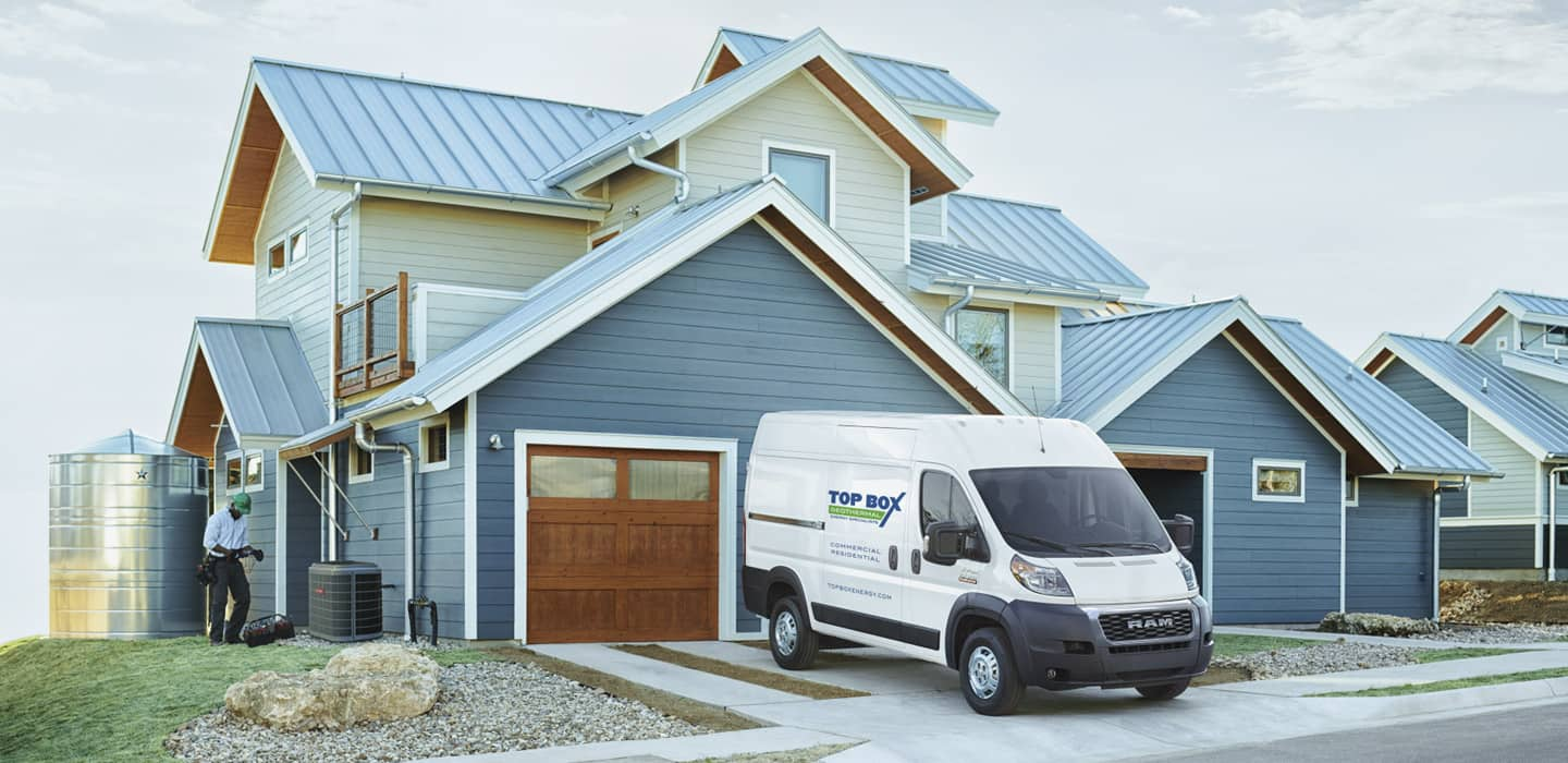 Display A 2020 Ram ProMaster Cargo Van with the logo of a geothermal company parked in the driveway of a home.
