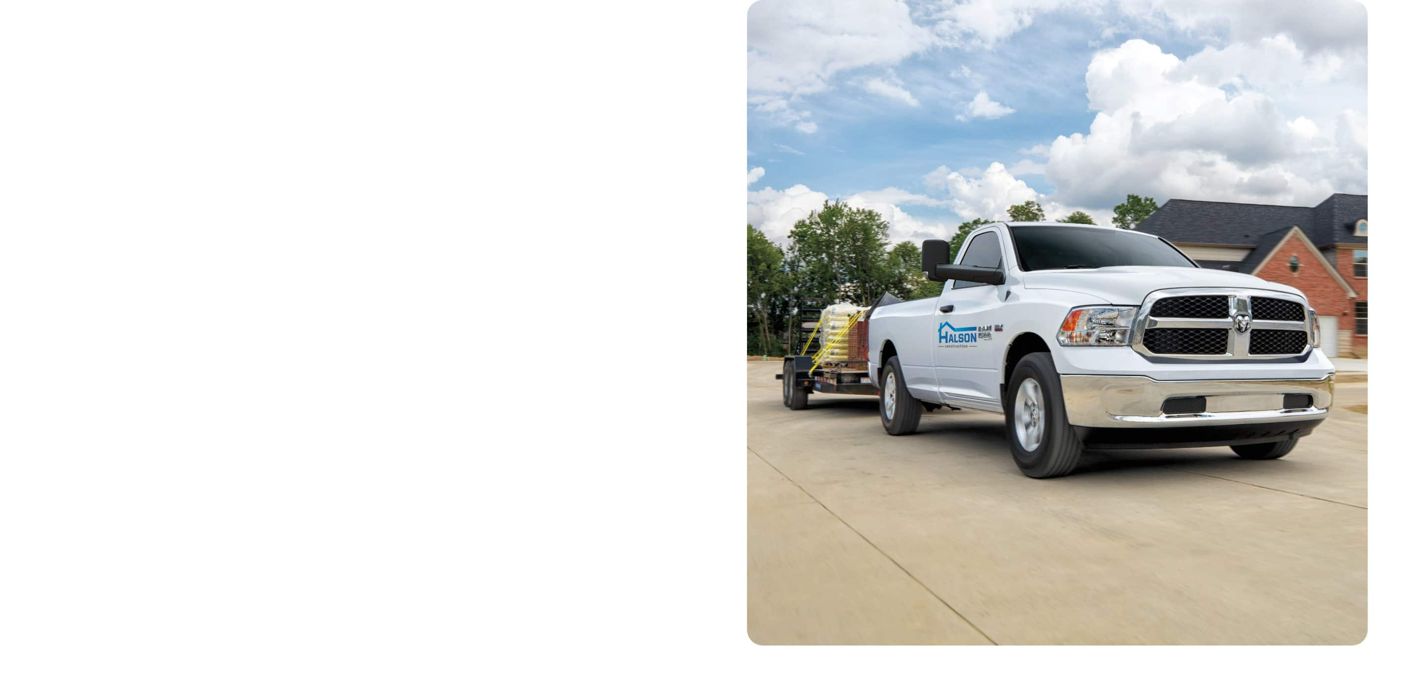 A 2021 Ram 1500 Classic with signage on the door, being driven through a neighborhood subdivision while towing a flatbed trailer loaded with construction materials.