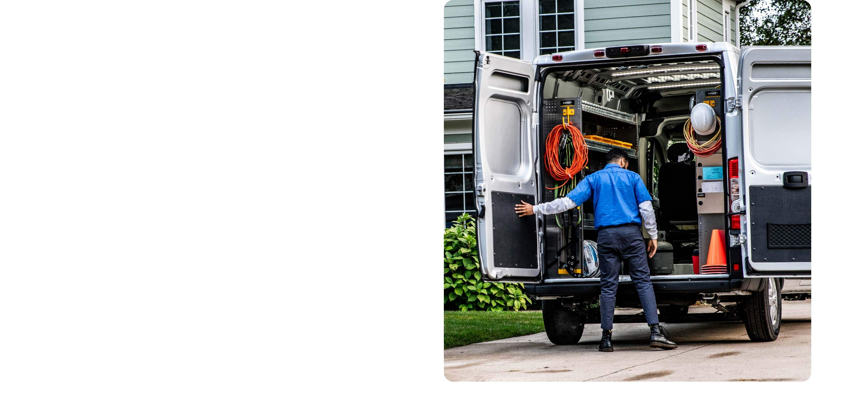 A man standing at the open rear doors of the 2021 Ram ProMaster, looking at the construction equipment arranged on the shelving and storage upfits inside.