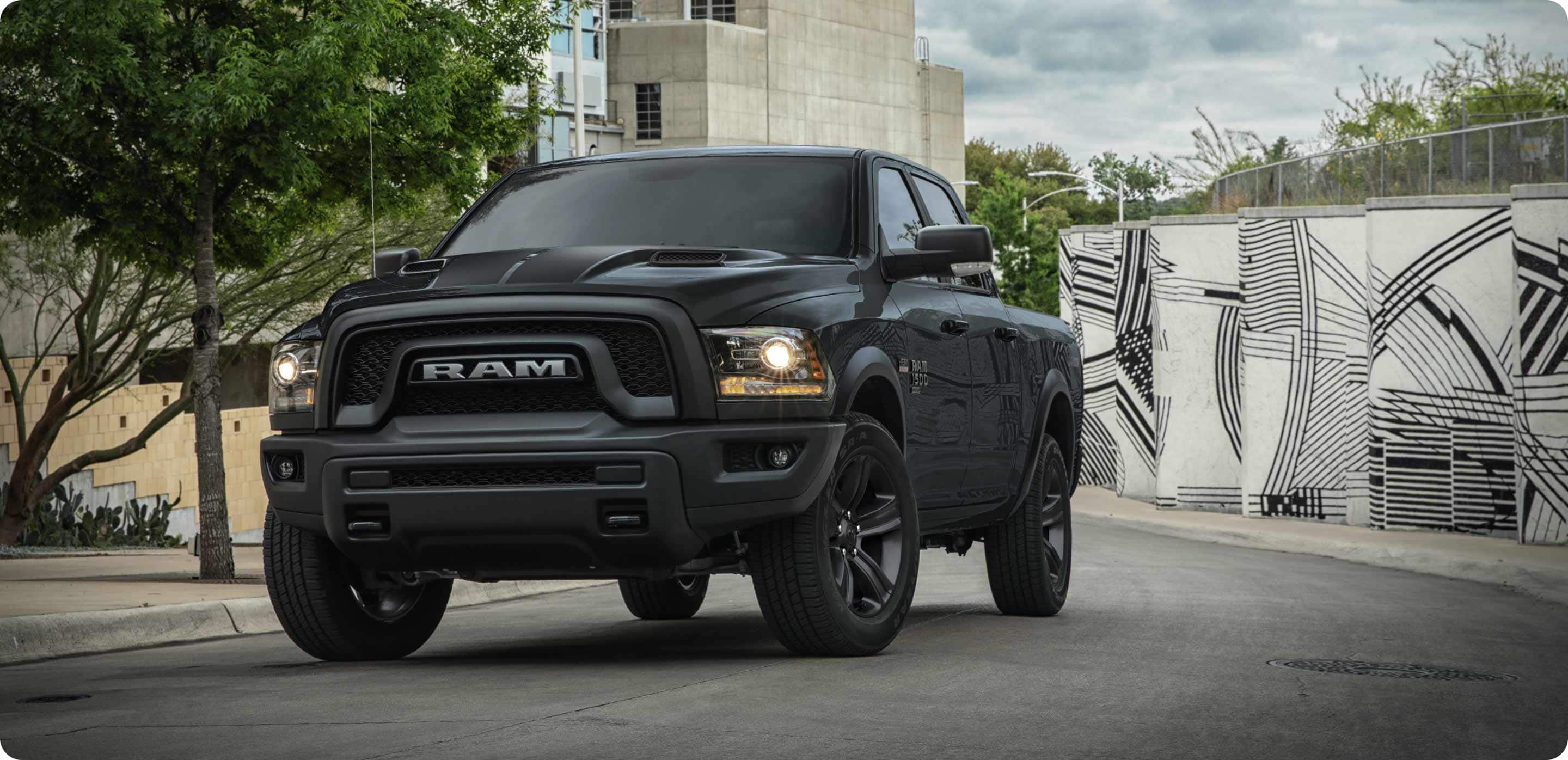 Display The 2021 Ram 1500 Classic Warlock being driven in an urban area with a large wall mural behind it.