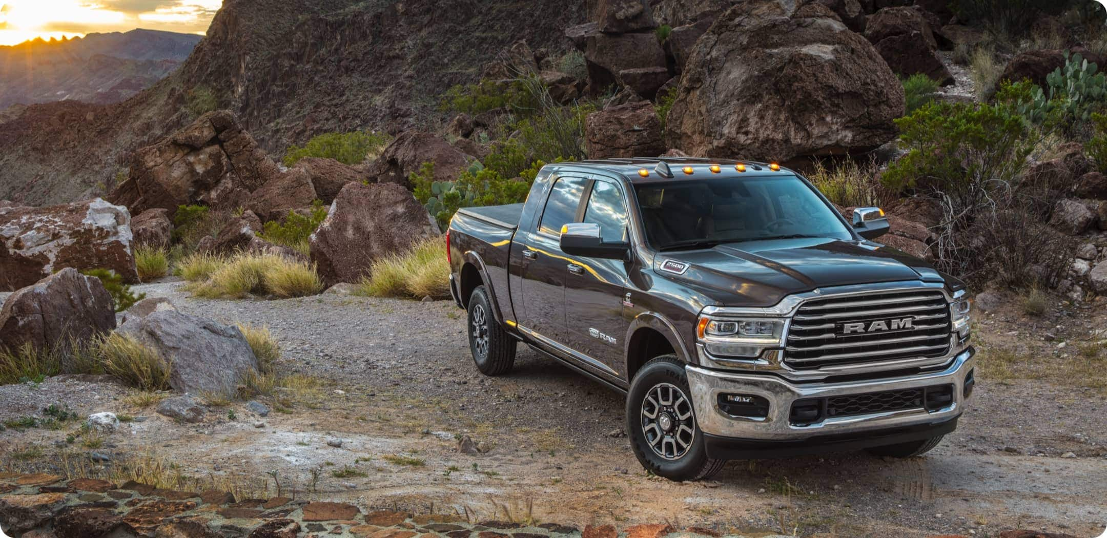 Display A 2021 Ram 2500 Limited Longhorn, parked on a trail in the mountains.