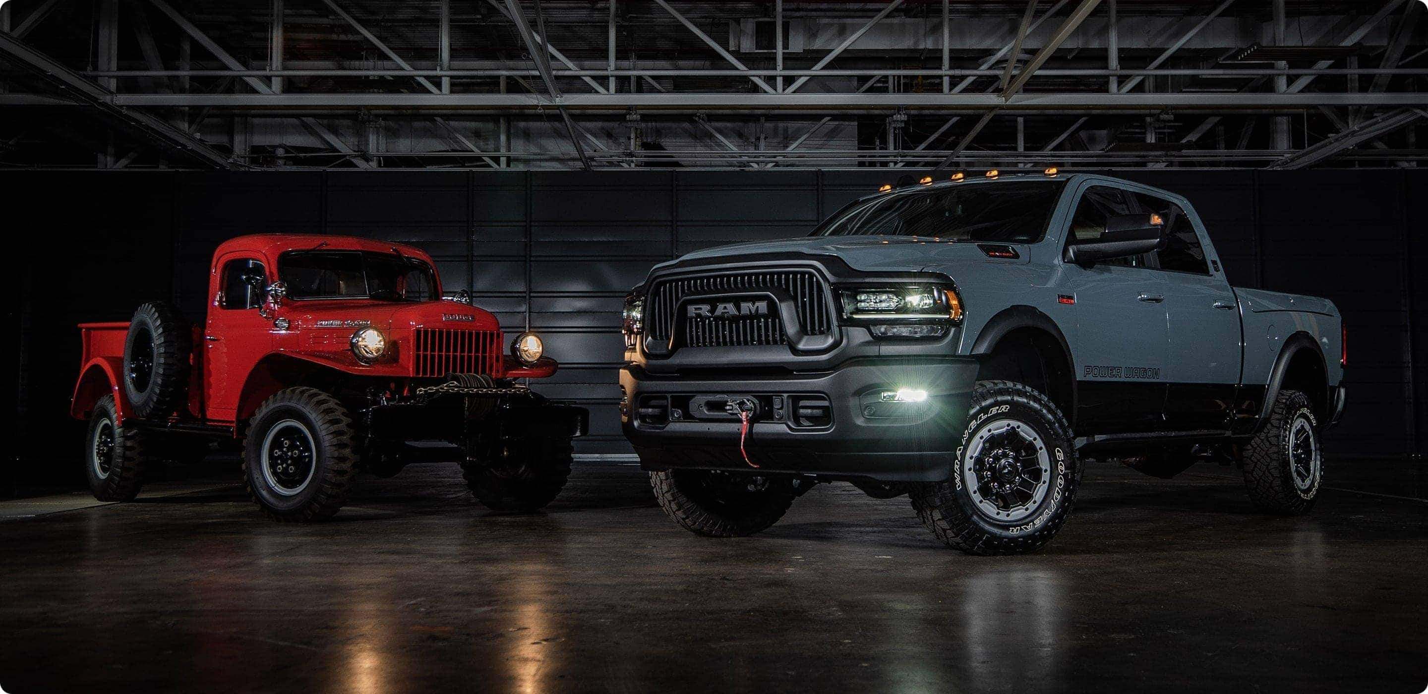 Display A classic 1954 Ram Power Wagon and the 2021 Ram 2500 Power Wagon 75th Anniversary Edition, both with their headlamps on, parked in a darkened industrial garage.