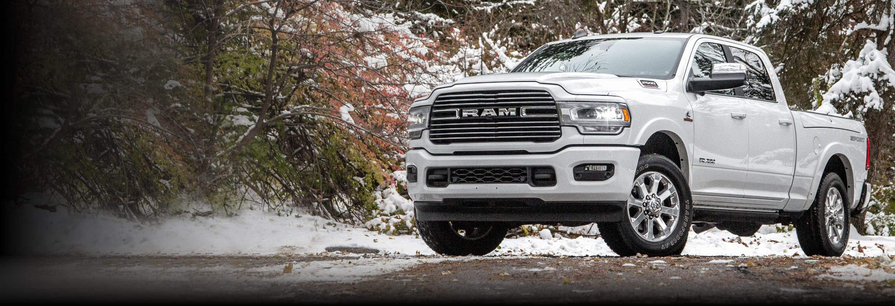 A 2021 Ram 2500 Laramie parked on a trail in snow-covered woods.