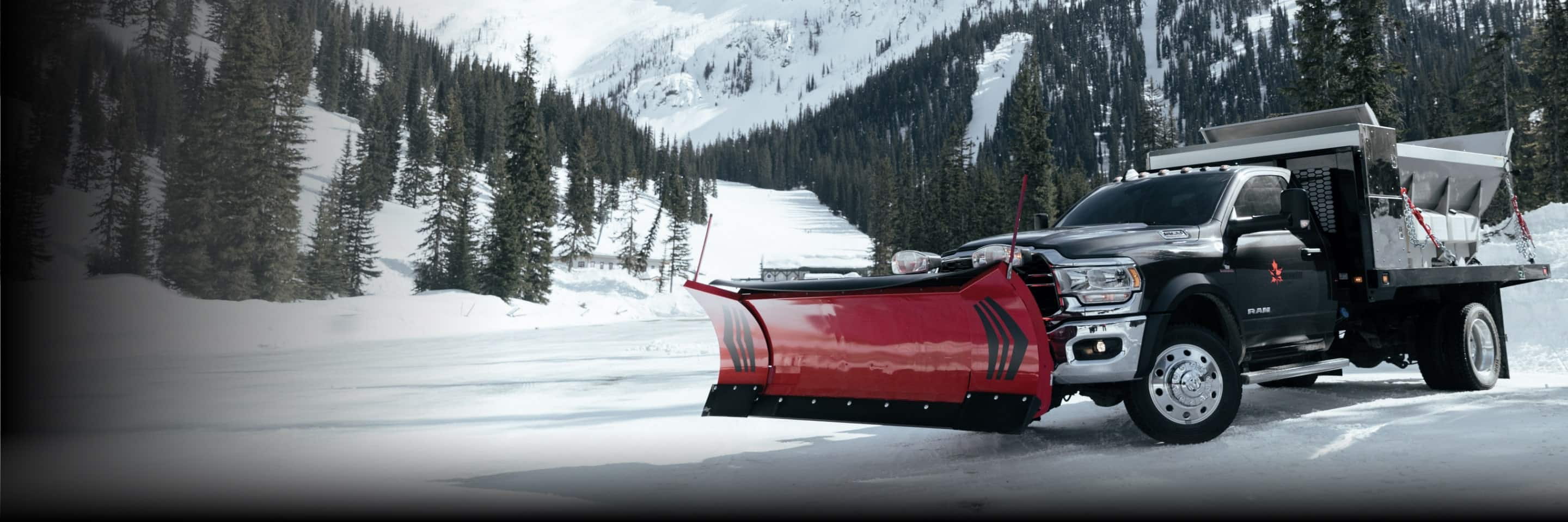 The 2021 Ram 5500 Chassis Cab with a snowplow upfit being driven on a mountain road.