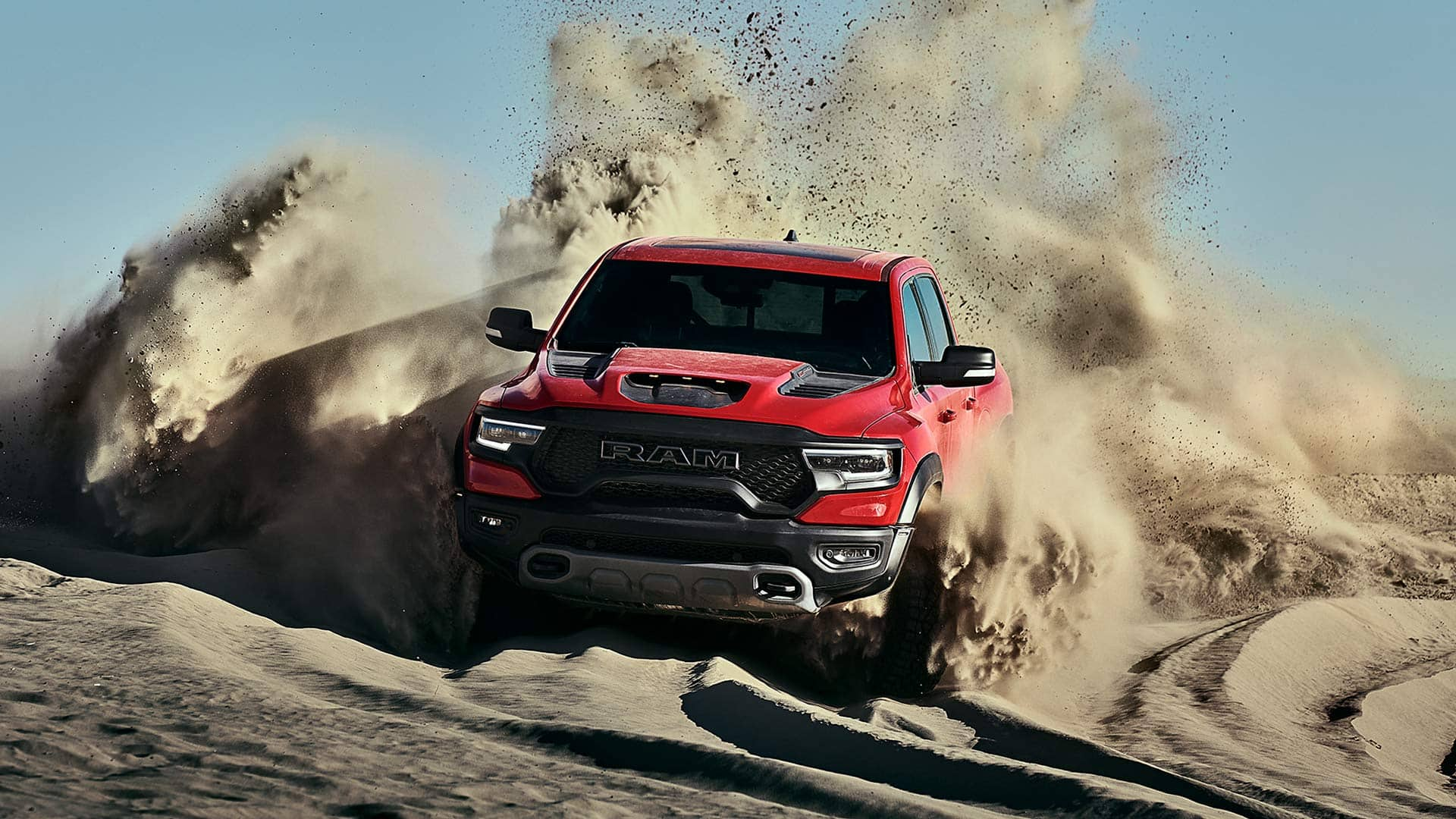 The 2021 Ram 1500 TRX being driven over a sand dune, churning up a large dust cloud.
