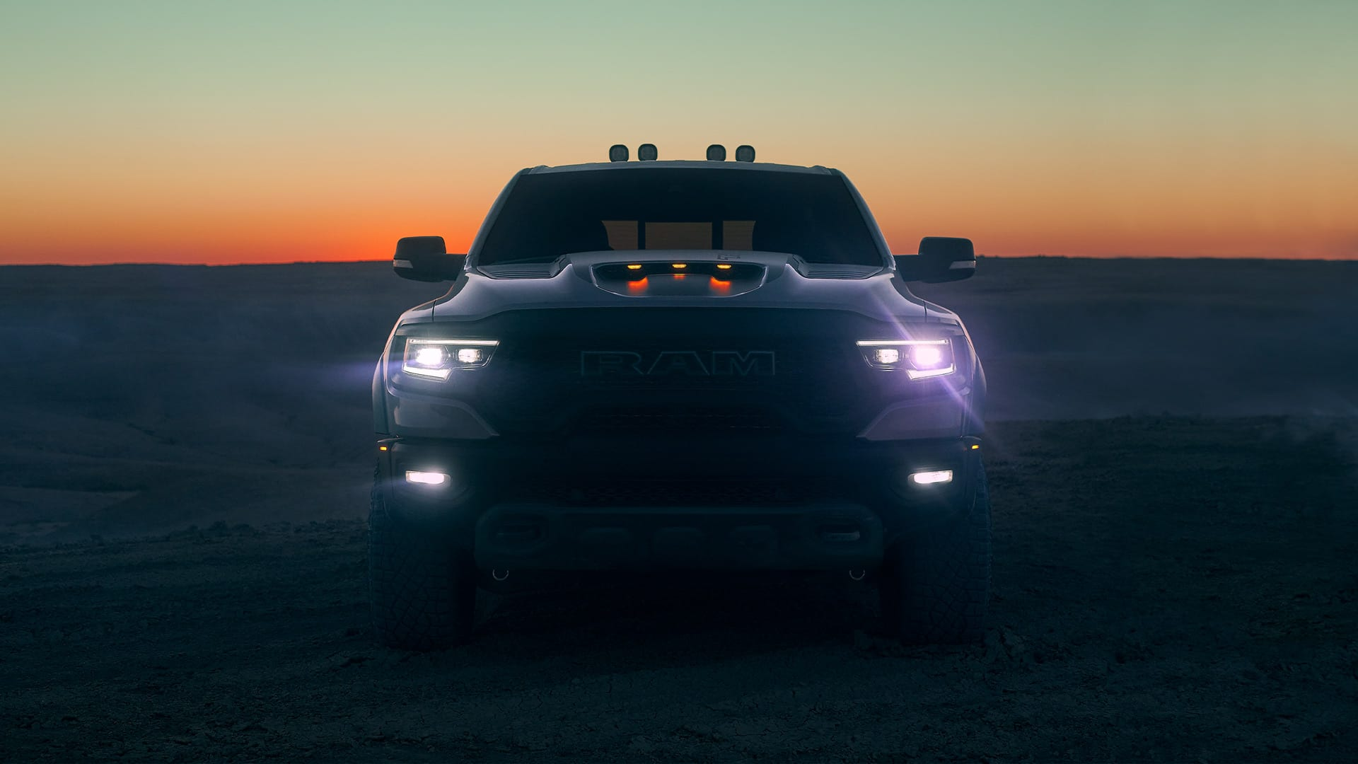 Display A head-on view of the 2021 Ram 1500 TRX at sunset with its headlamps, high beams and fog lamps lit.