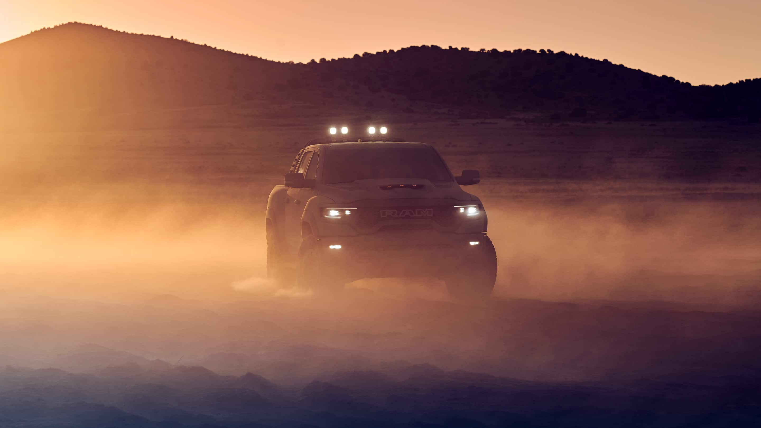 The headlamps of the 2021 Ram 1500 TRX lit as it is driven off-road at sunset.