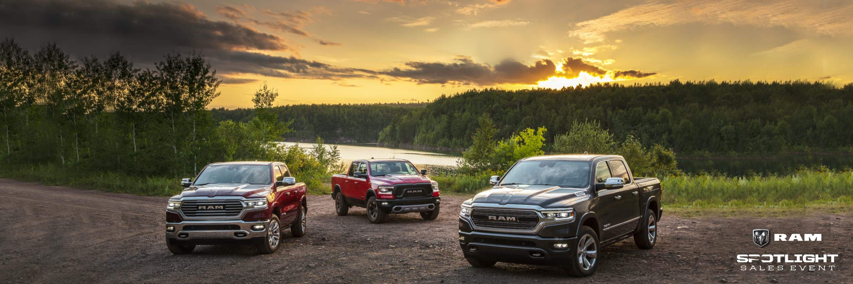Three 2021 Ram 1500 models: a Limited Longhorn, Rebel and Limited parked beside a lake with the sun rising over a forest of trees in the background. Ram Spotlight Sales Event logo.