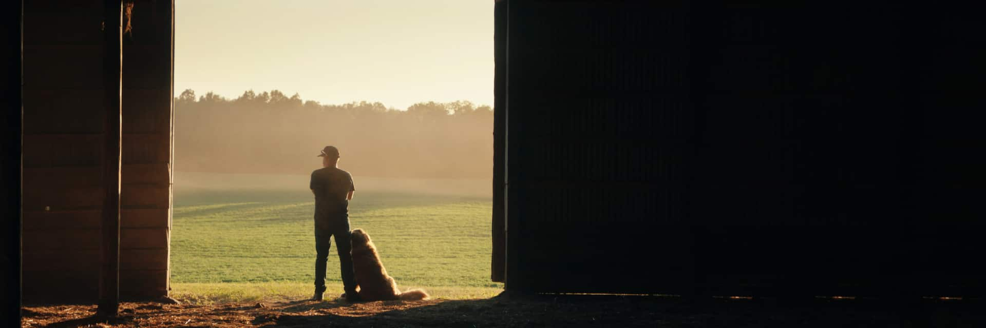 A man with his dog standing at the entrance of a barn, looking out at the vast open field at sunrise.