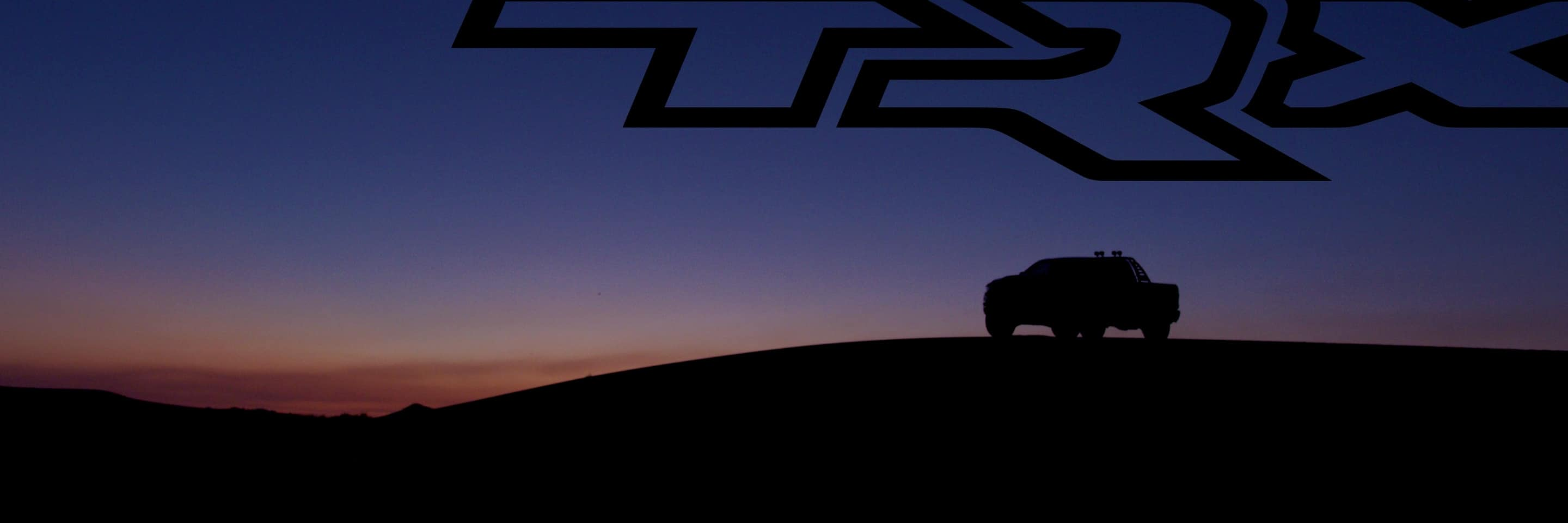 A prominent TRX logo overhead with a 2021 Ram 1500 TRX silhouetted against a sunset sky.