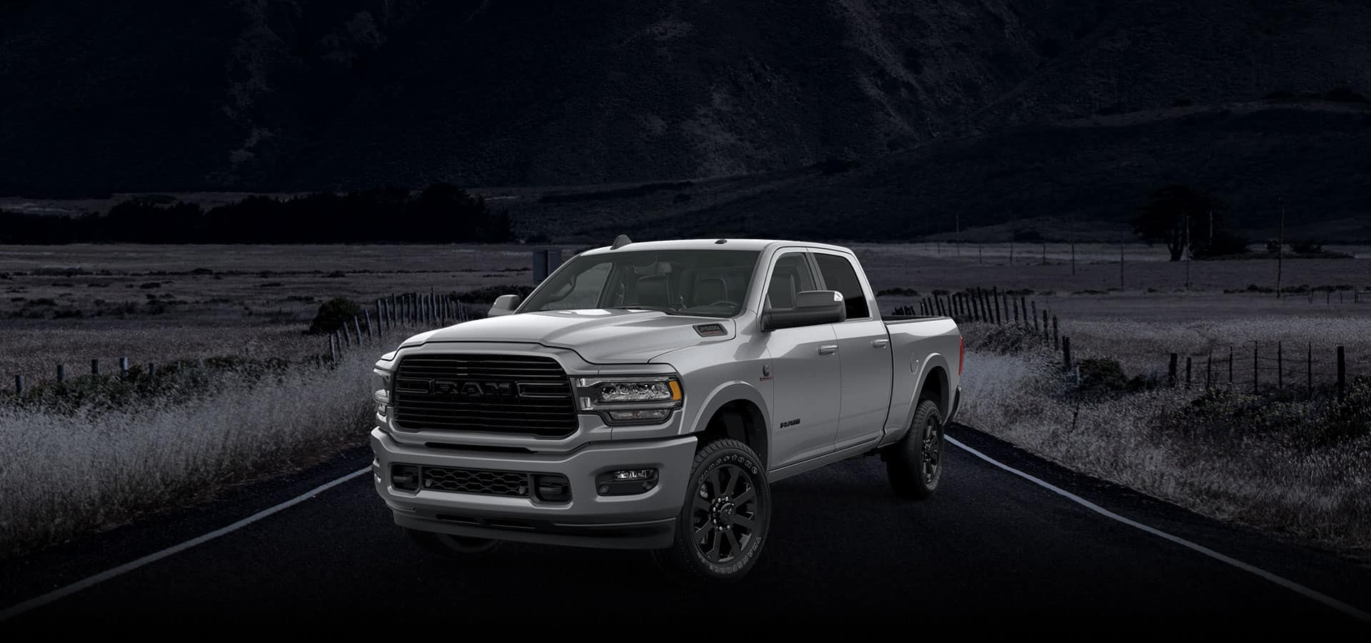 A 2019 Ram 2500 Night Edition on a road at night in farmland with the background presented in black and white.