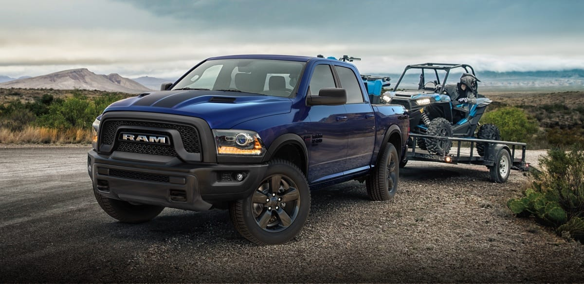Ram 1500 Classic Warlock towing an ATV on a flatbed trailer. Properly secure all cargo. Always tow within the vehicle's