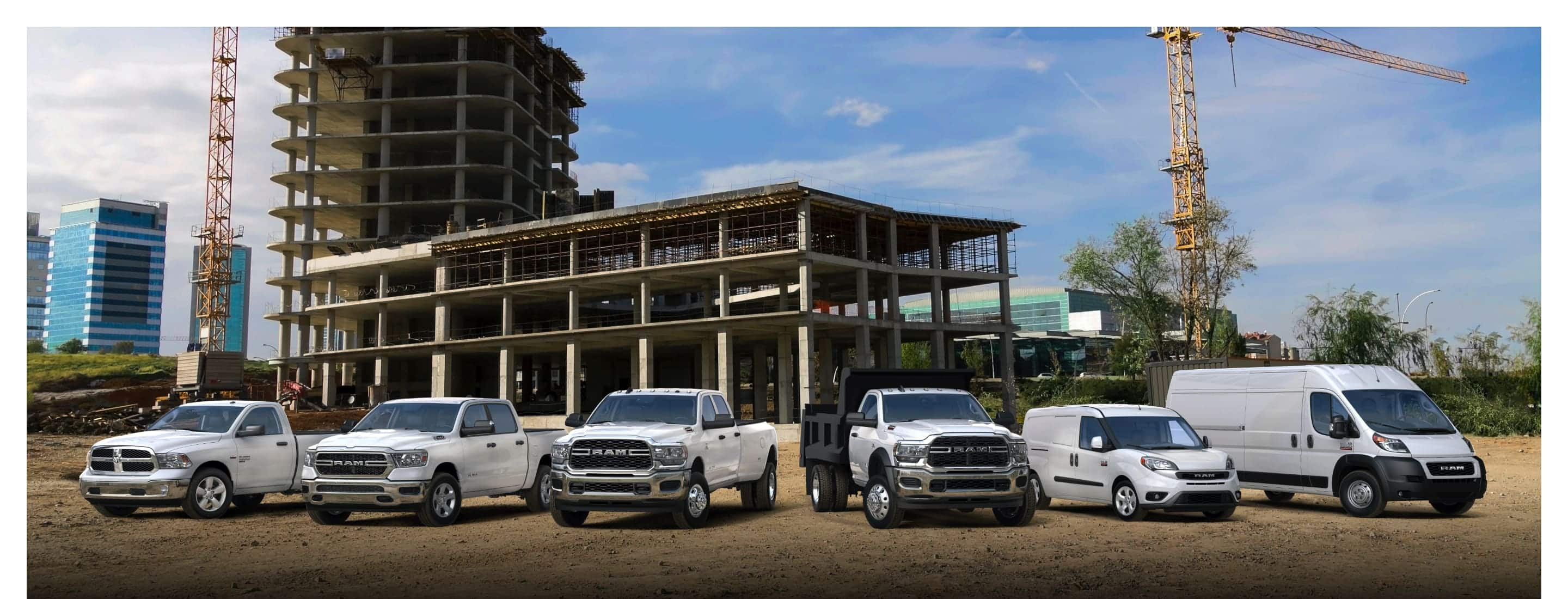 The 2021 Ram lineup parked at a commercial construction site. From left to right: four Tradesman models--a Ram 1500 Classic, Ram 1500, Ram 3500 and Ram 5500, followed by a Ram ProMaster City SLT Cargo Van and a Ram ProMaster 2500 Cargo Van.
