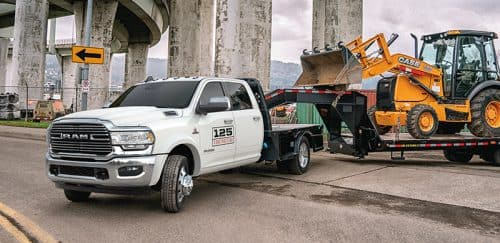 Ram Chassis Cab towing a construction vehicle on a flat bed.