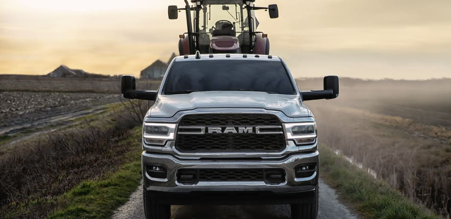 Display A 2019 Ram 2500 Tradesman with the Chrome Appearance Package being driven on a dirt road near a farm. A piece of heavy farming machinery is in the bed of the truck.