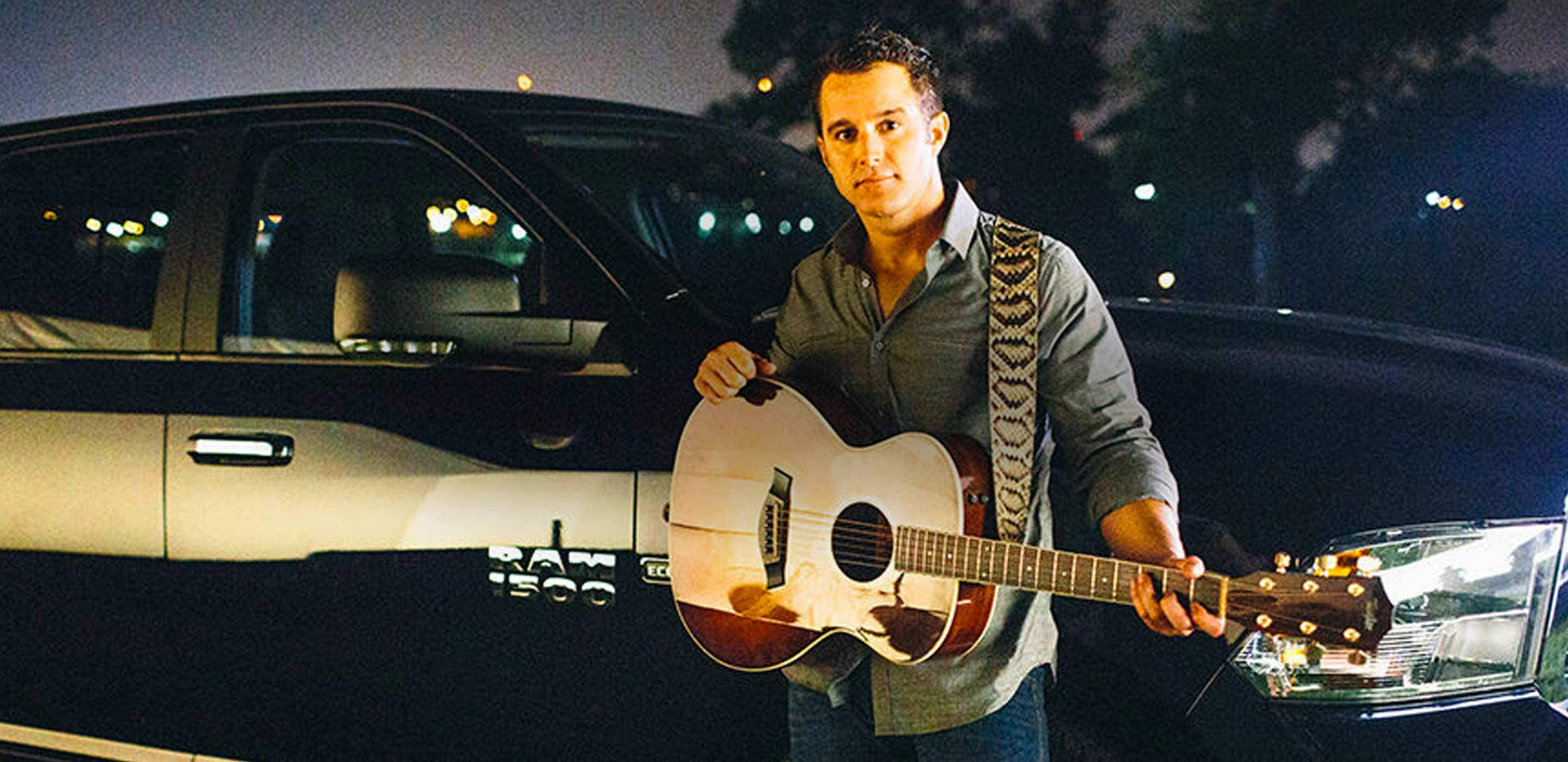 Display Country recording artist Easton Corbin holding a guitar and standing next to a Ram 1500 pickup.