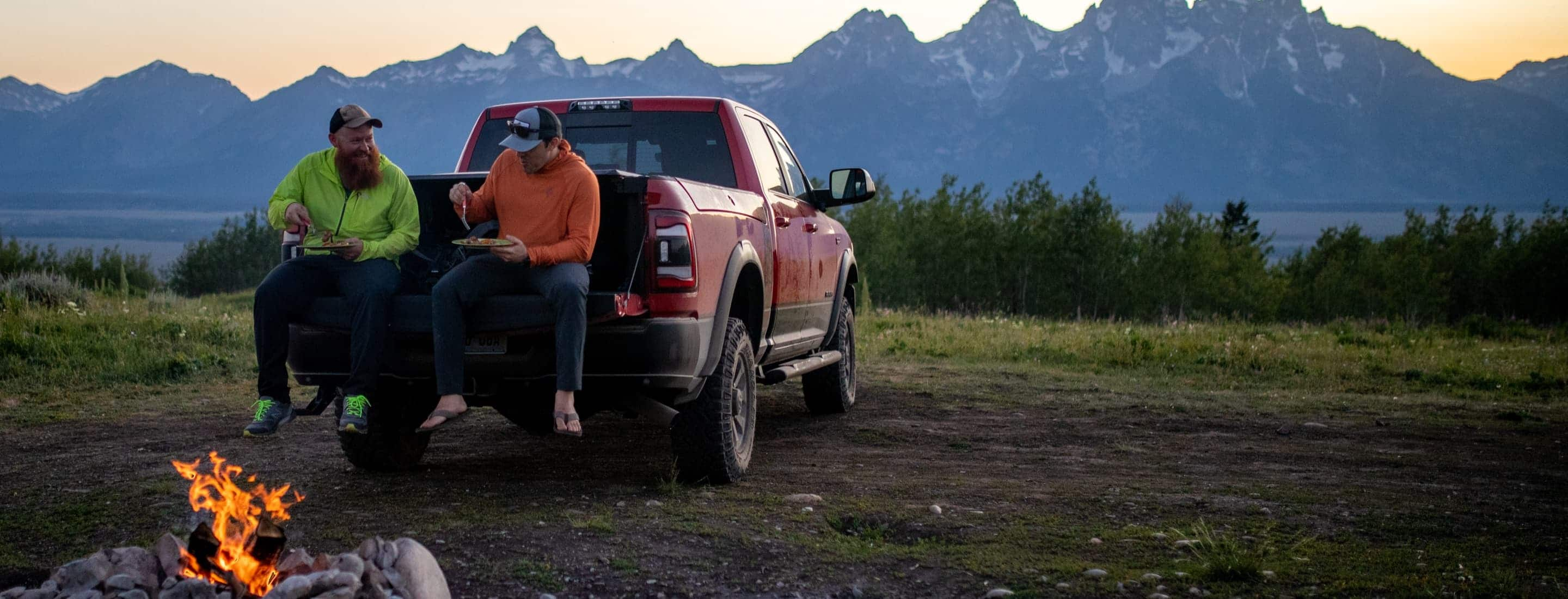Jake Frank and Andy Austin sitting on the lowered tailgate of Jake's 2019 Ram 2500, eating dinner.