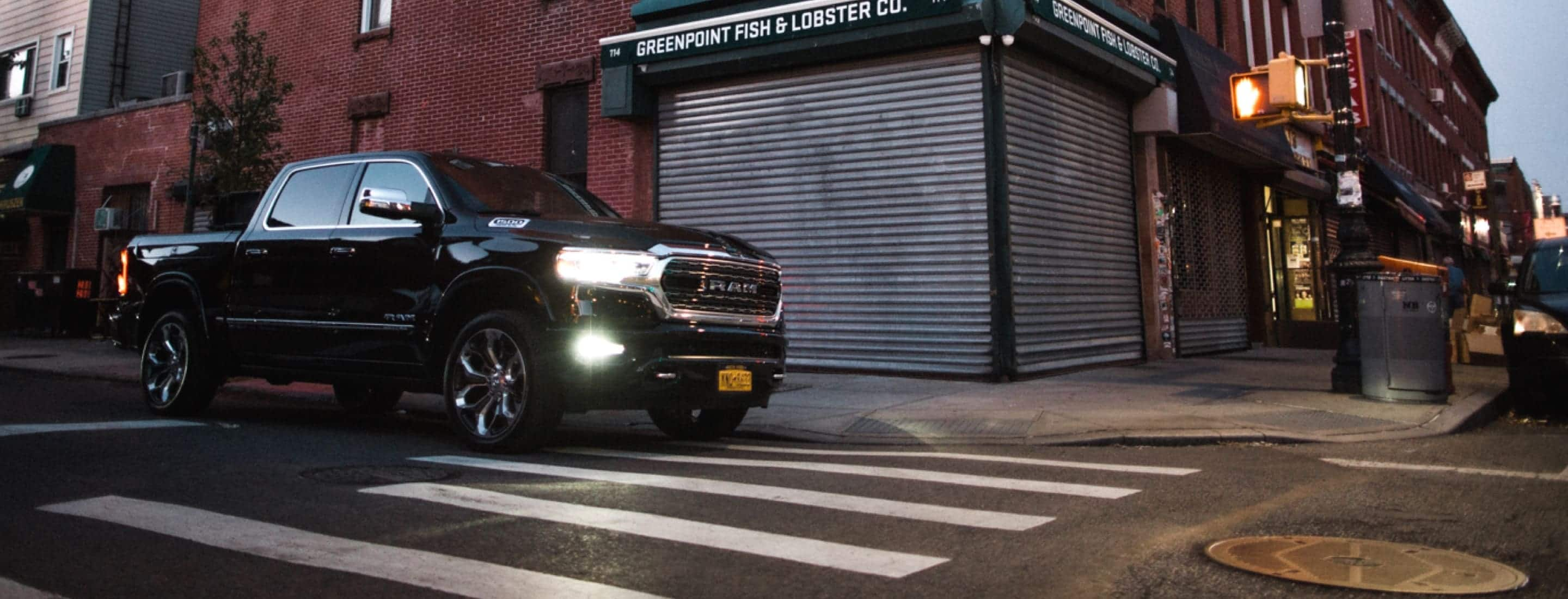 A 2019 Ram 1500 Limited parked on the curb beside Greenpoint Fish and Lobster Co.